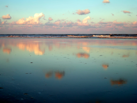 Beachscape with clouds reflecting in wet sand near dusk in late summer on Tybee Island, Georgia, USA