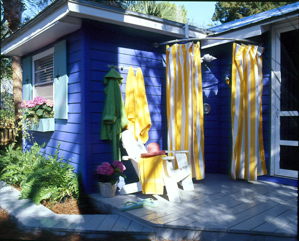 Cheerful Yellow-Striped Curtains Hang from an Outdoor Shower Built into the Corner of a Deck
