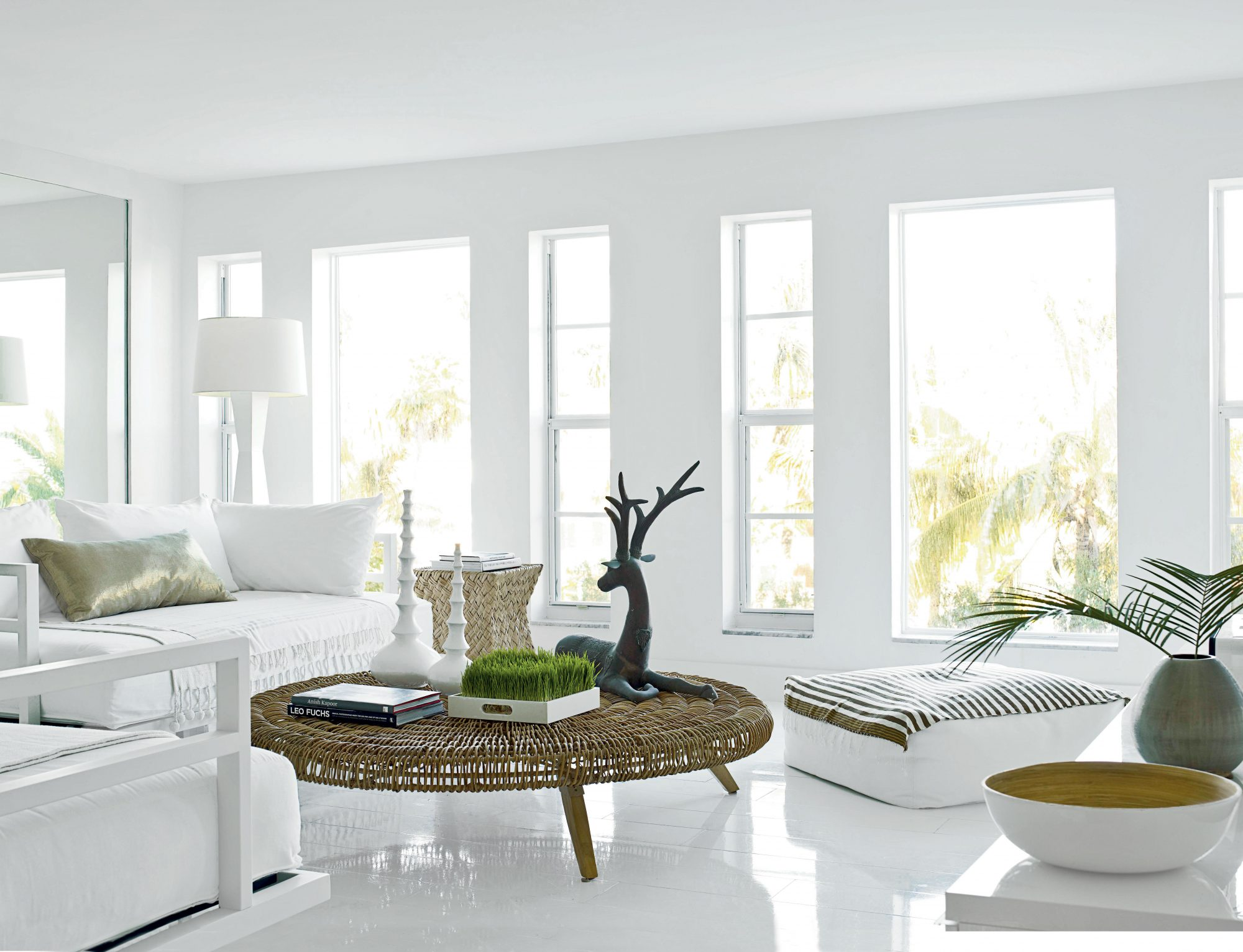 A bold piece of furniture—such as this dark, round wicker table—brings unexpected warmth and personality to the room.