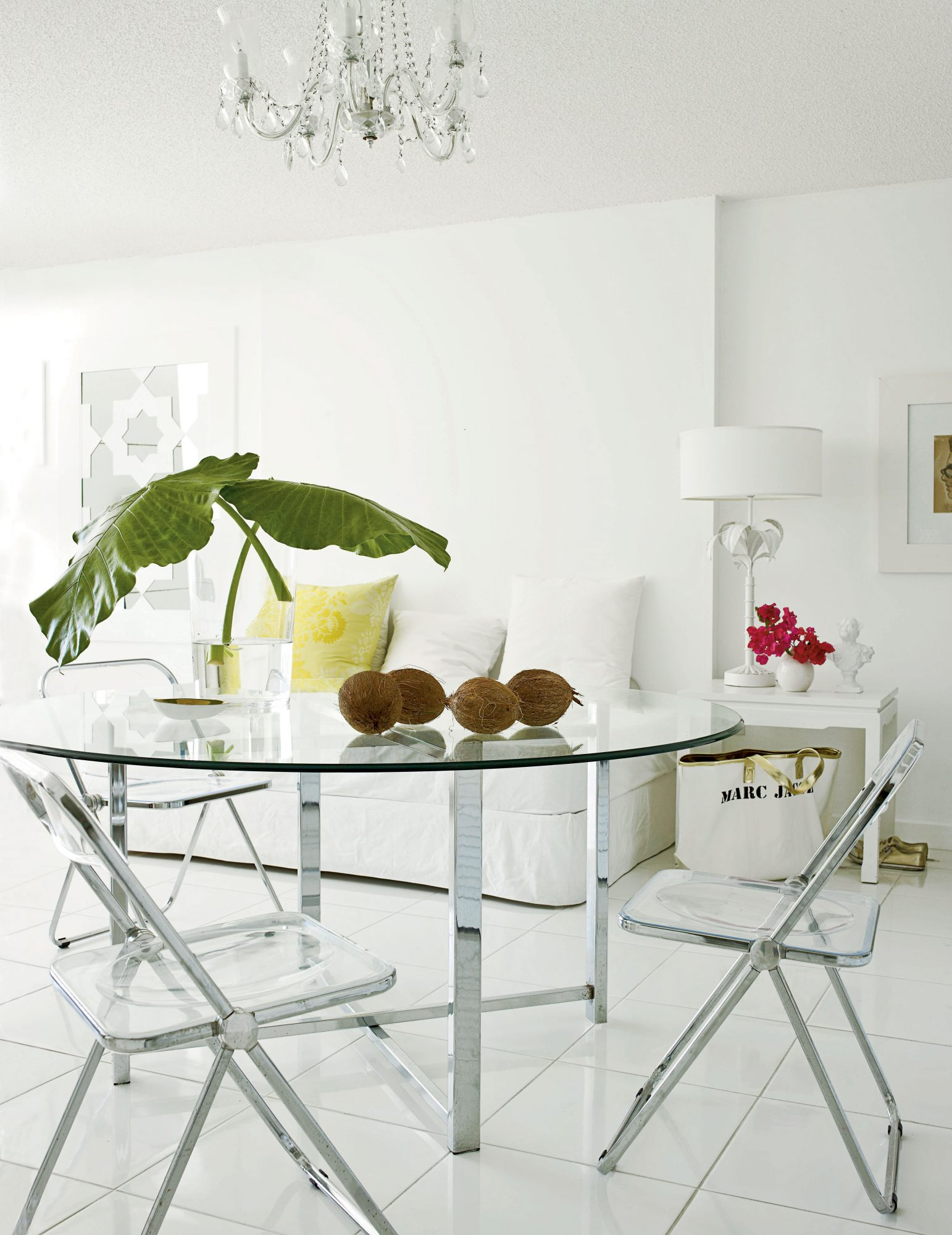 Two acrylic folding chairs paired with a glass table create a streamlined dining area without overwhelming the compact space.