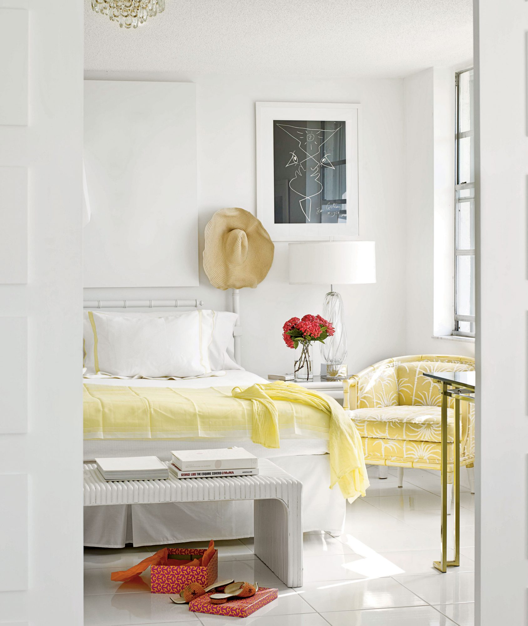 A vintage glass lamp, palm-print chair, and a sunny-hued bed linen add a flirty feel to this all-white bedroom.