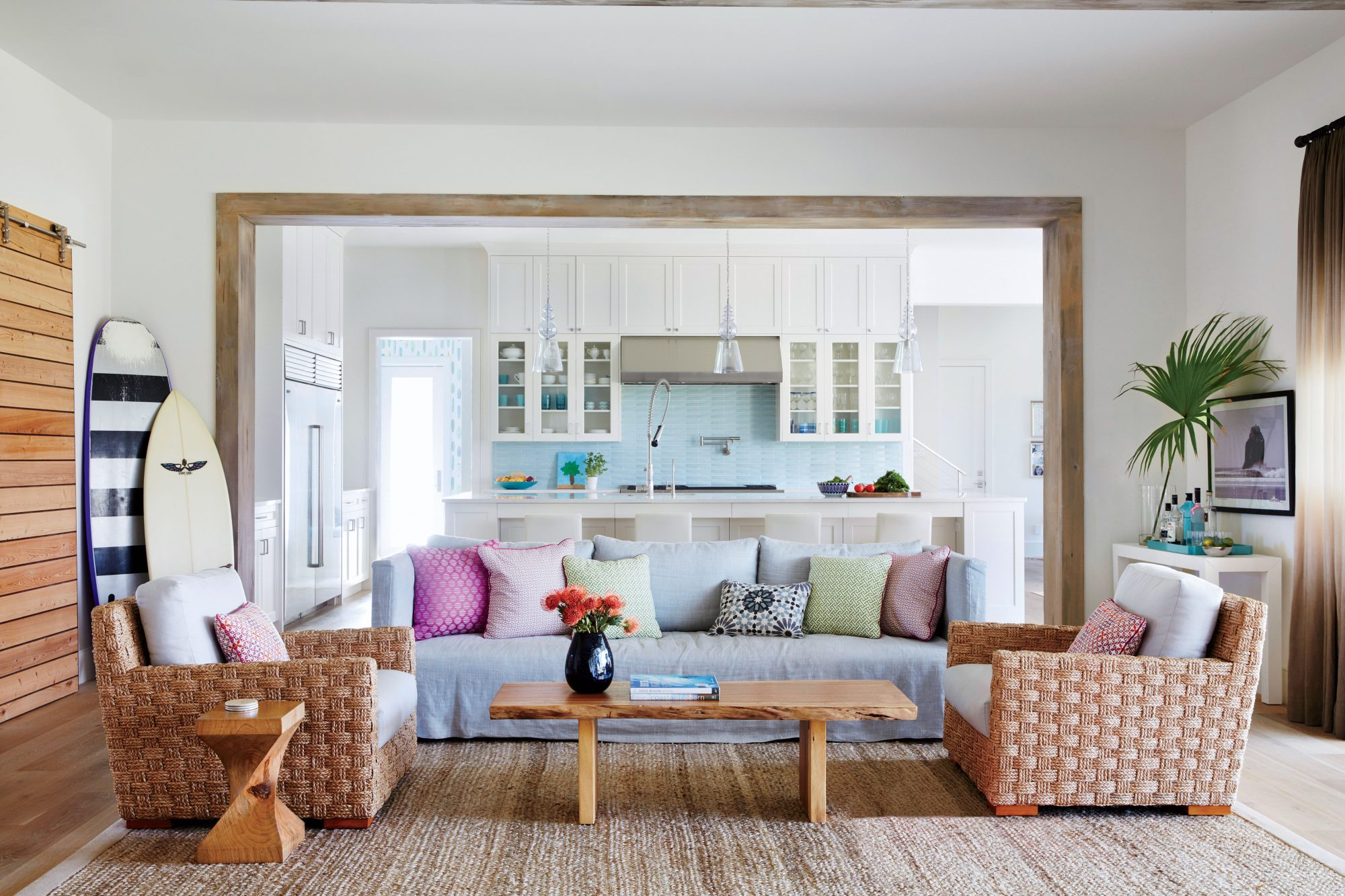 Inside, they opted for a central living hub, where broad pass-throughs between rooms keep the living room, kitchen, and breakfast nook visually connected. Rustic washed-pine trim frames the spaces and sets a laid-back vibe in line with their beachy locale