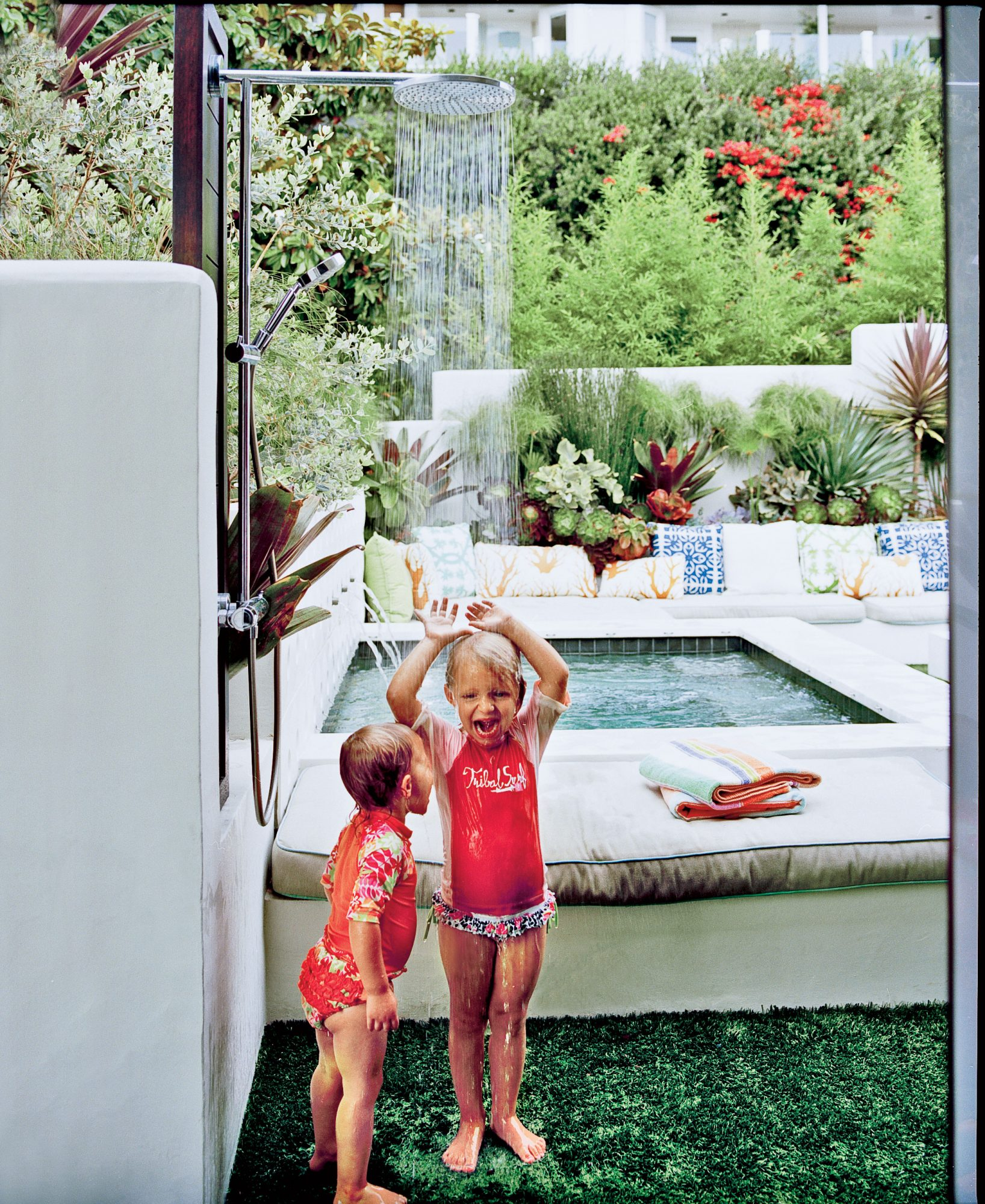 "For a kid-friendly shower floor, consider replacing potentially slippery tiles with artificial grass. Water drains through the turf into pipes below. Covering the rest of the courtyard in the faux material keeps the look cohesive and clearly says ""no shoe"