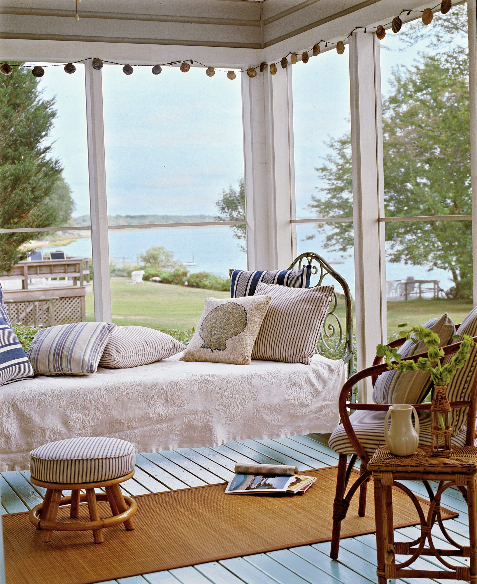 With views of a serene pond beyond, this screened sleeping porch, off the rear of a renovated Long Island beach cottage, is a plum spot for enjoying the salt-spiked air and a beach read. The antique iron bed, blue-green-painted wood floors, and rattan fur
