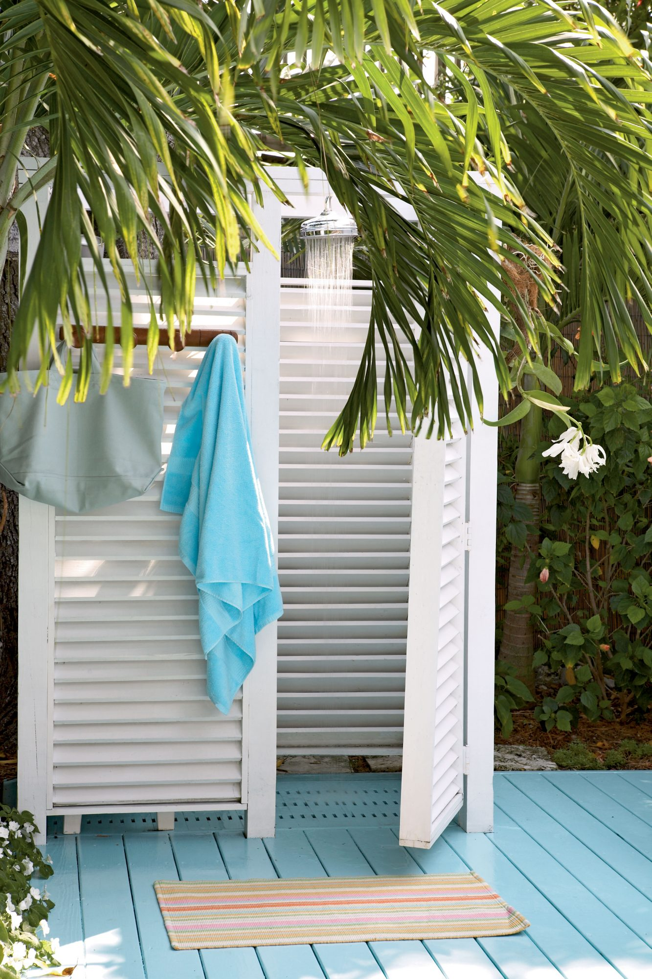 white shutter dividers surround an outdoor shower