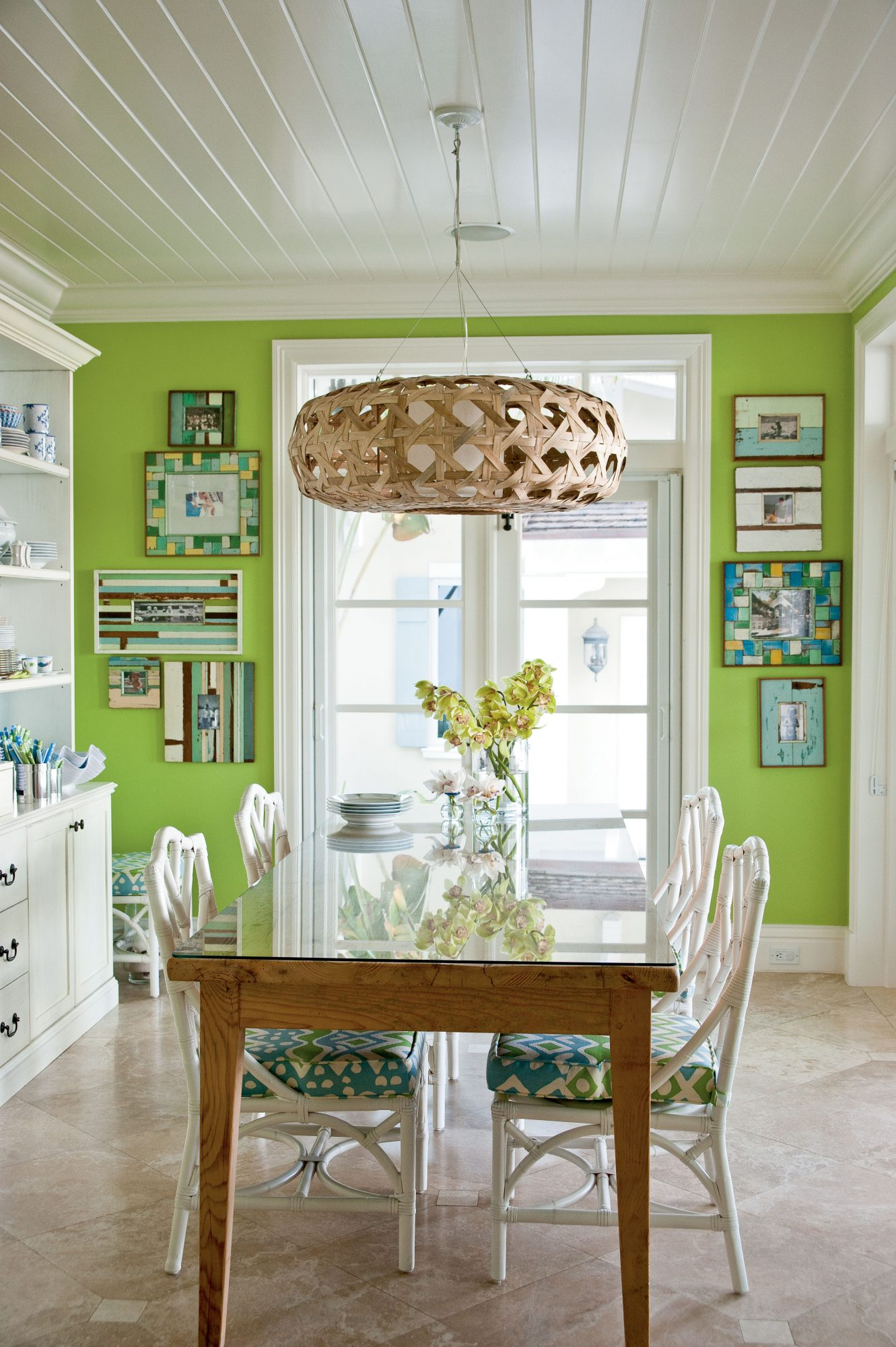 The home's playful, bright color palette comes alive in the dining room, where a grass green hue covers the walls. White wicker chairs and graphic picture frames help subdue the bold shade.
