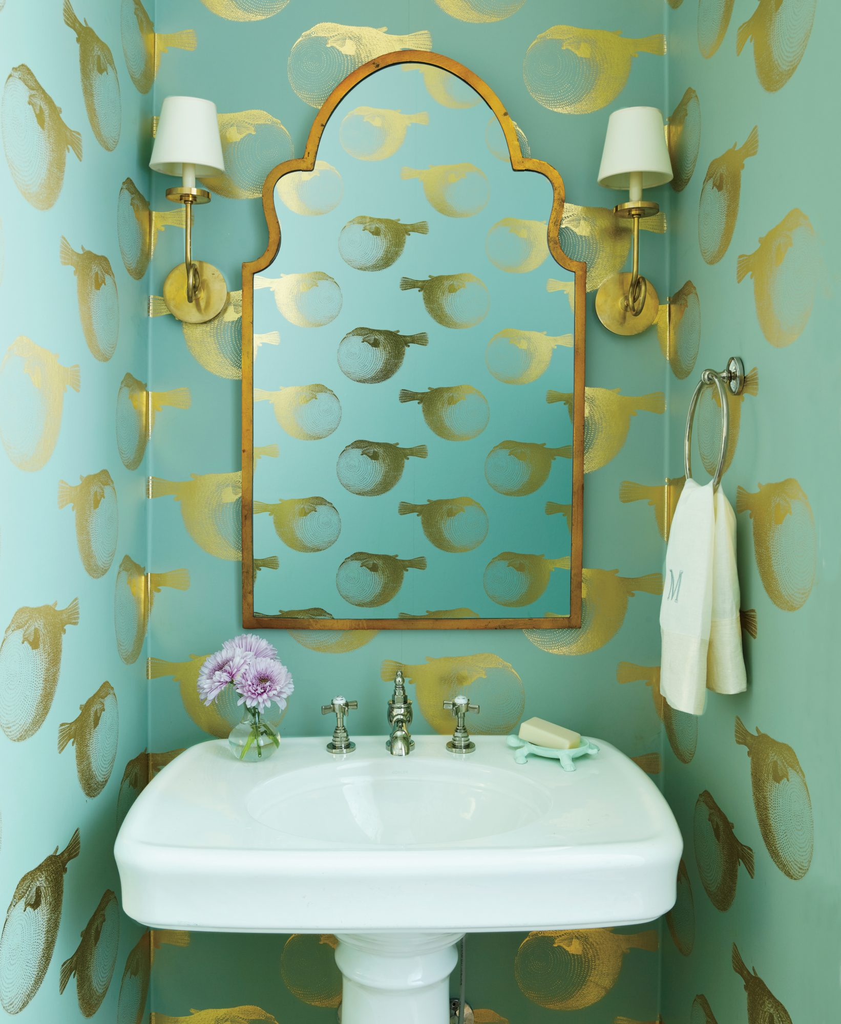 """My personality, the way I like to decorate, is a little whimsical,"" says Elizabeth. ""And powder rooms are great places for doing something that's a little bit ""out there."""" Enter the aqua, watery world of a cheeky, gilded puffer fish ""swimming"" around th"