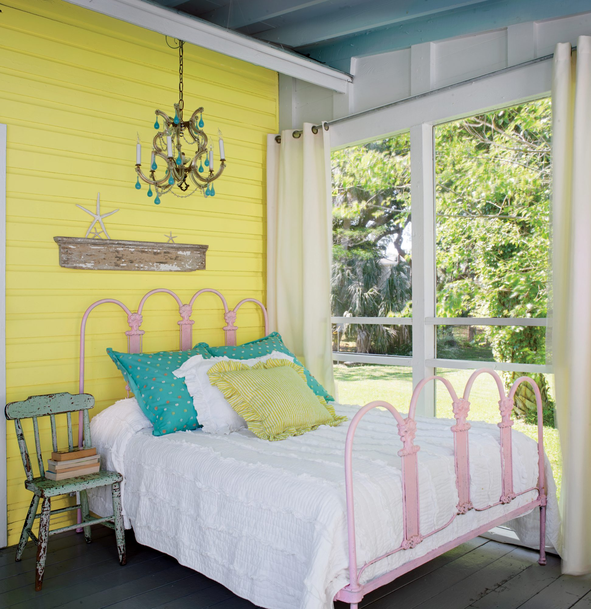 Designer Jane Coslick converted this sunshine-yellow beach cottage's original veranda into a sweet dreams-worthy sleeping porch. Rustic elements boast unexpected touches, from the antique iron bed painted pink to the weathered chair used as storage for bo