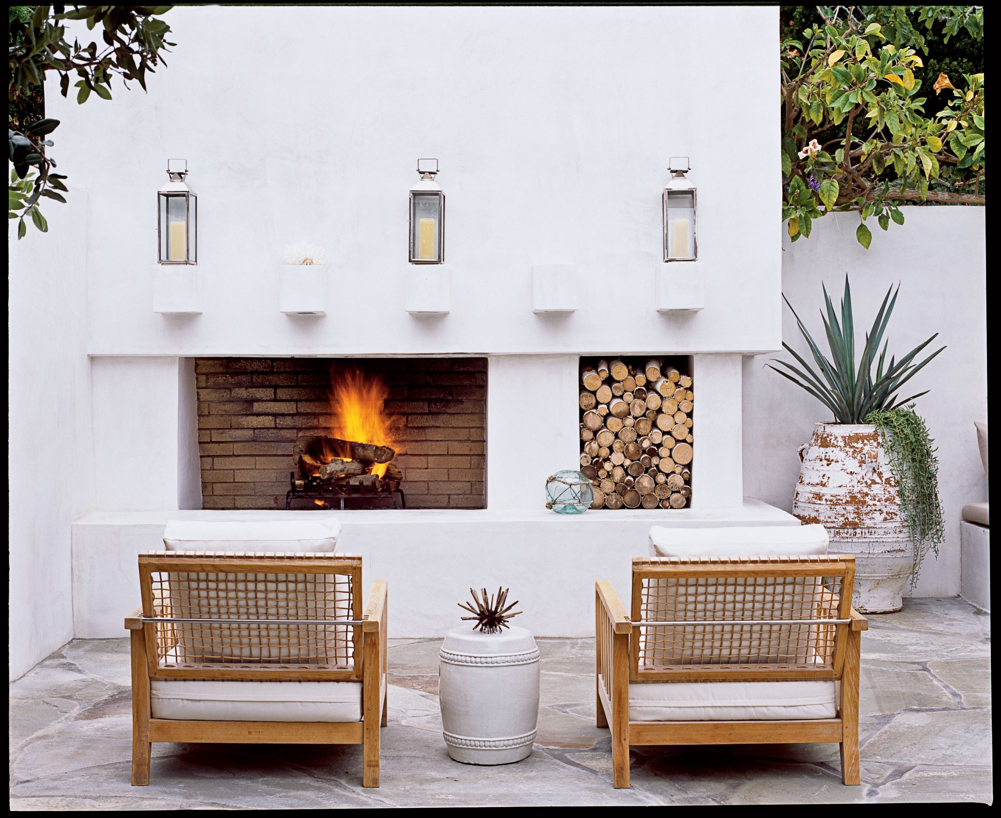 A simple outdoor fireplace makes a patio or porch functional year-round. Plush cushions on comfy wide-backed chairs make it the perfect place for enjoying a cocktail on a cool evening.