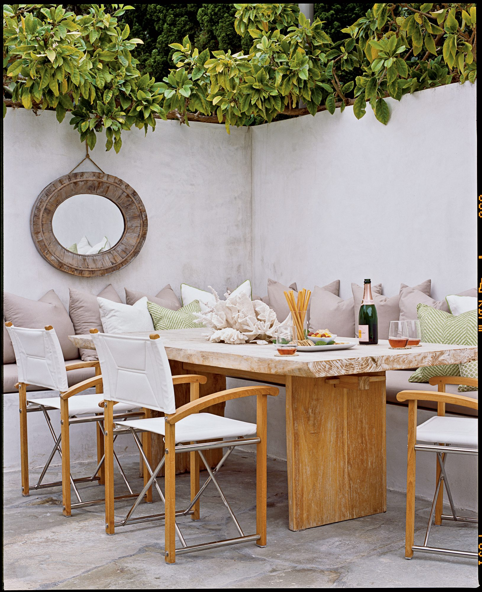 This simple, neutral dining table makes an ideal spot for seaside entertaining thanks to generous seating and ample cushions. A decorative mirror and plush pillows complete the look.