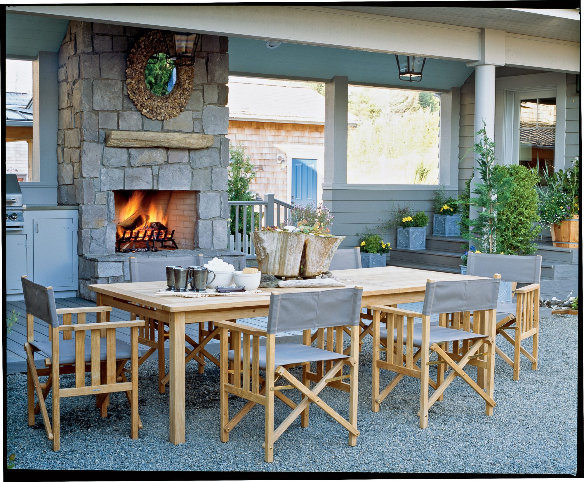 Pebble flooring and a glowing fireplace give this patio a warm, natural feel. A wooden table, director-style chairs, and a tree trunk centerpiece enhance the rustic vibe.