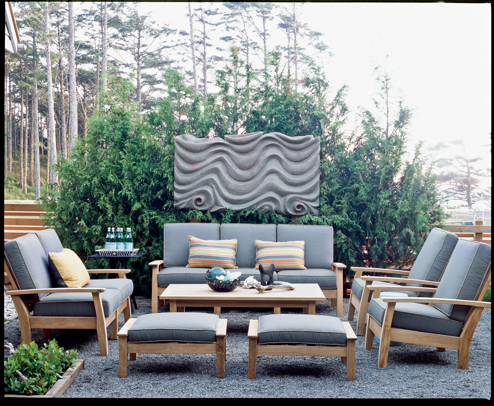 Pea gravel creates the illusion of an area rug on this modern patio. A dramatic sculpture creates a focal point and lends interest to this outdoor living room.