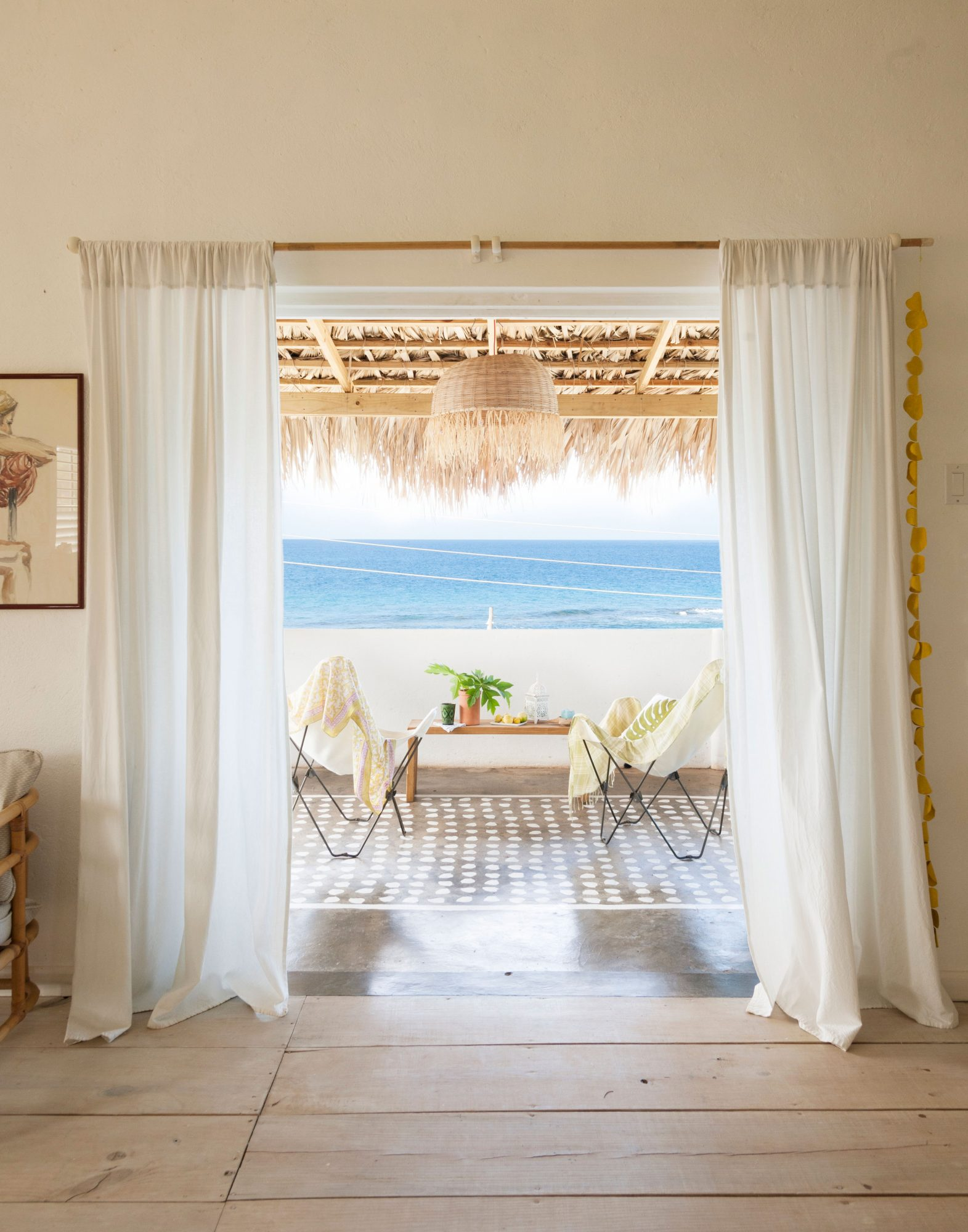 On this balcony in Treasure Beach, Jamaica, the décor is simple. Butterfly chairs and a coffee table are accented with eye-catching concrete floors and a bamboo pendant.