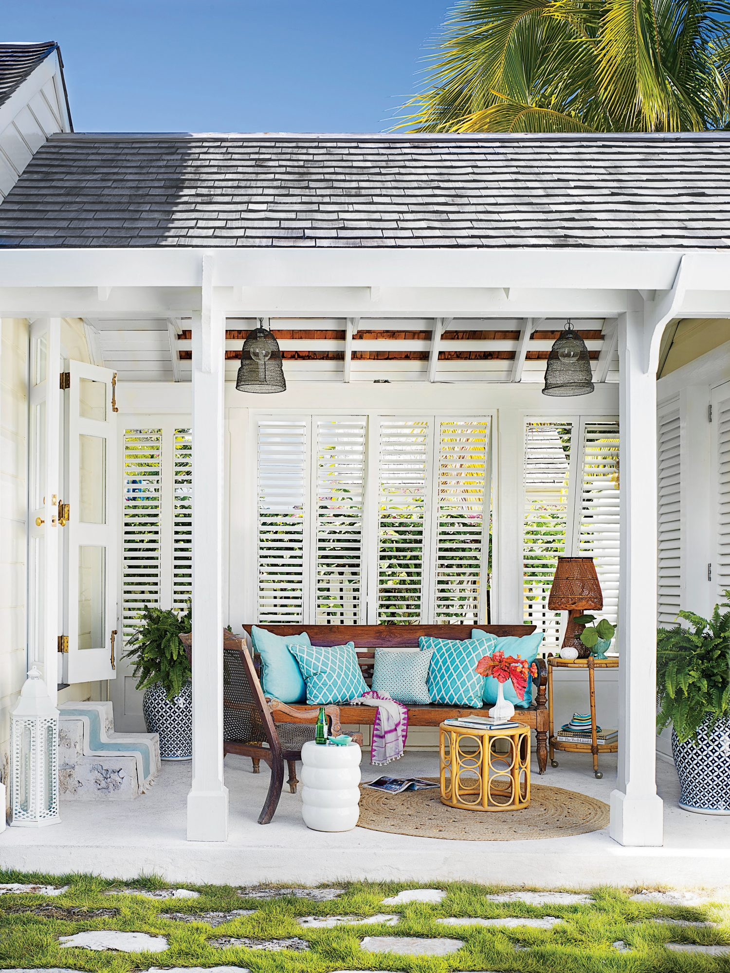 A vintage teak daybed by Columbus and Cook takes center stage in this Bahamas outdoor living room. Louvered shutters lend privacy while allowing the island breeze to flow.