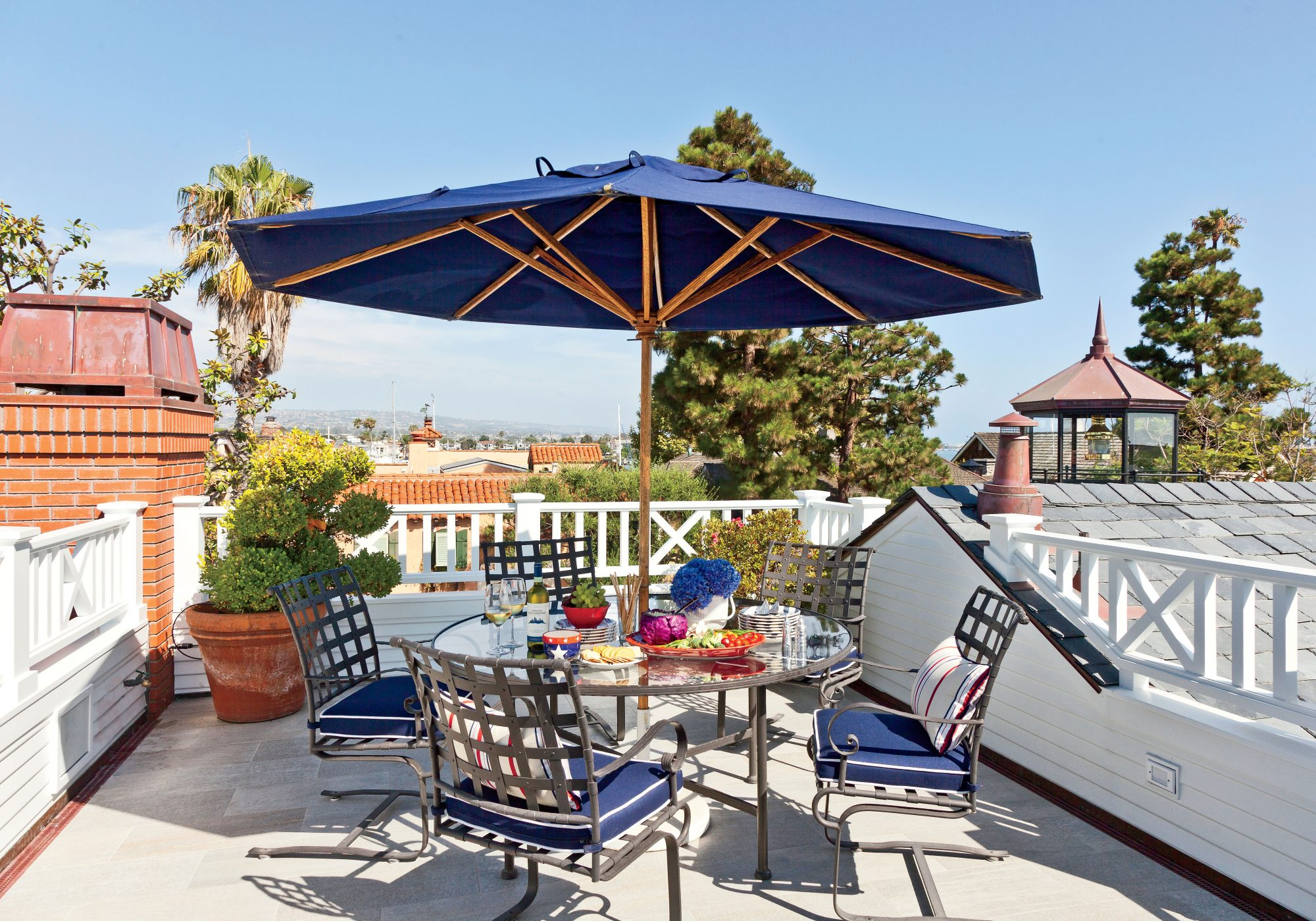 This sun-drenched rooftop deck sits right next to a lantern room replica atop a lighthouse-inspired home in Newport Beach, California.