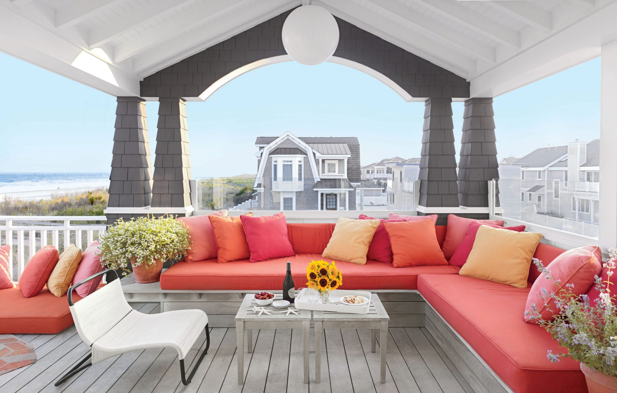 An L-shaped built-in bench with plush cushions and pillows, plus a duo of appetizer-ready tables, makes for an alfresco-ready hangout on the Jersey Shore.