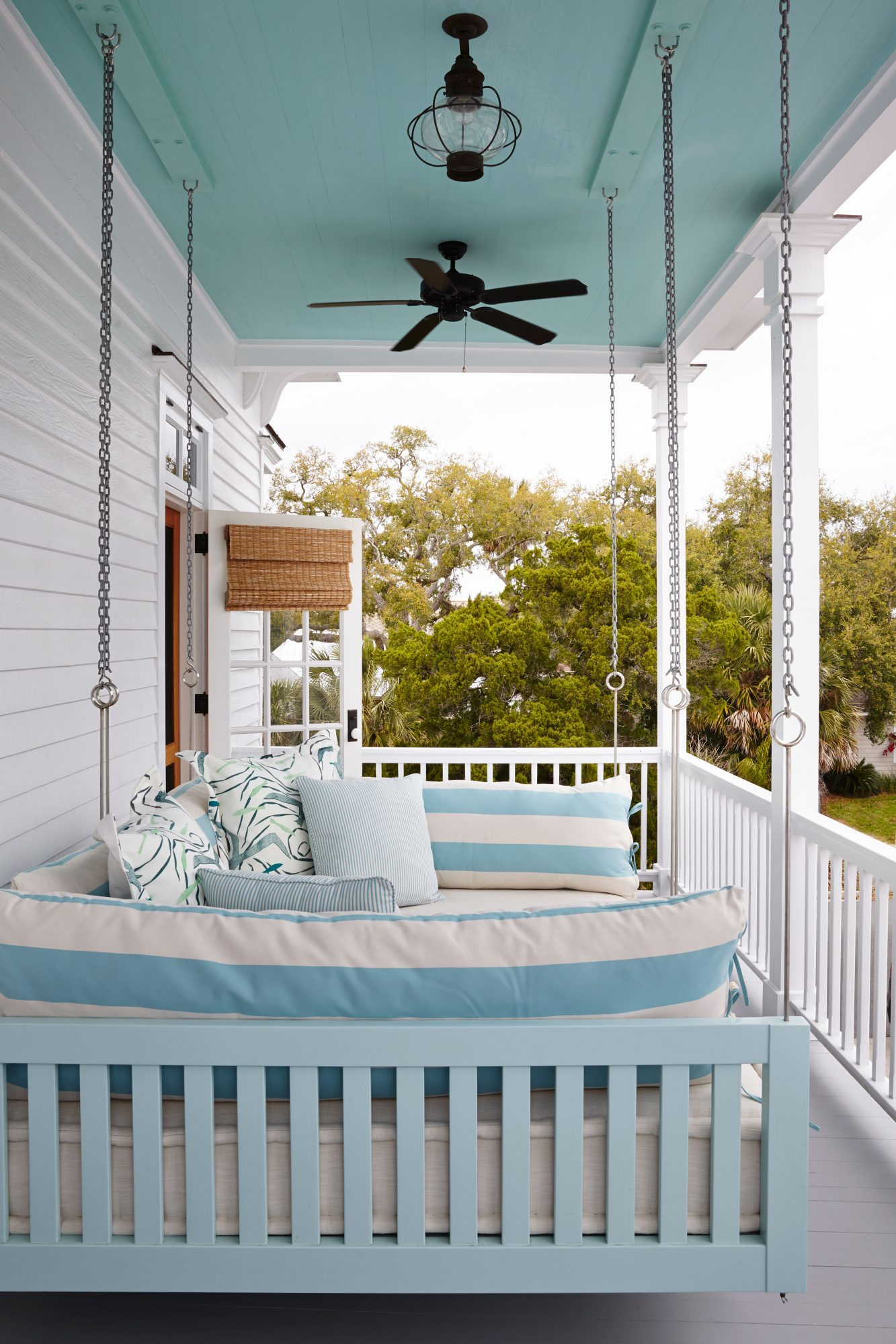 Robin's Egg blue is repeated on the painted ceiling and striped indoor/outdoor fabrics that adorn this King-size hanging bed overlooking the Gulf on Cedar Key, Florida.