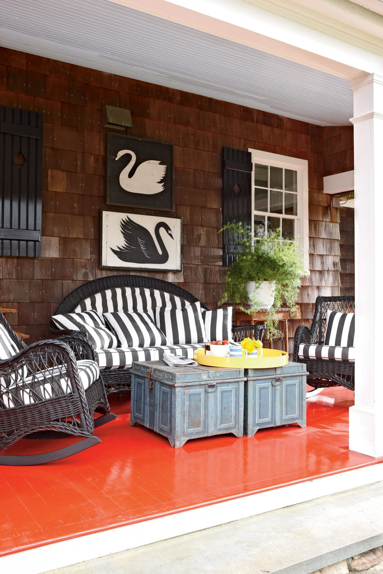 On a whimsical play of a classic color combination, a glossy red floor contrasts with black-and-white accents such as the striped outdoor cushions and decorative wall art.