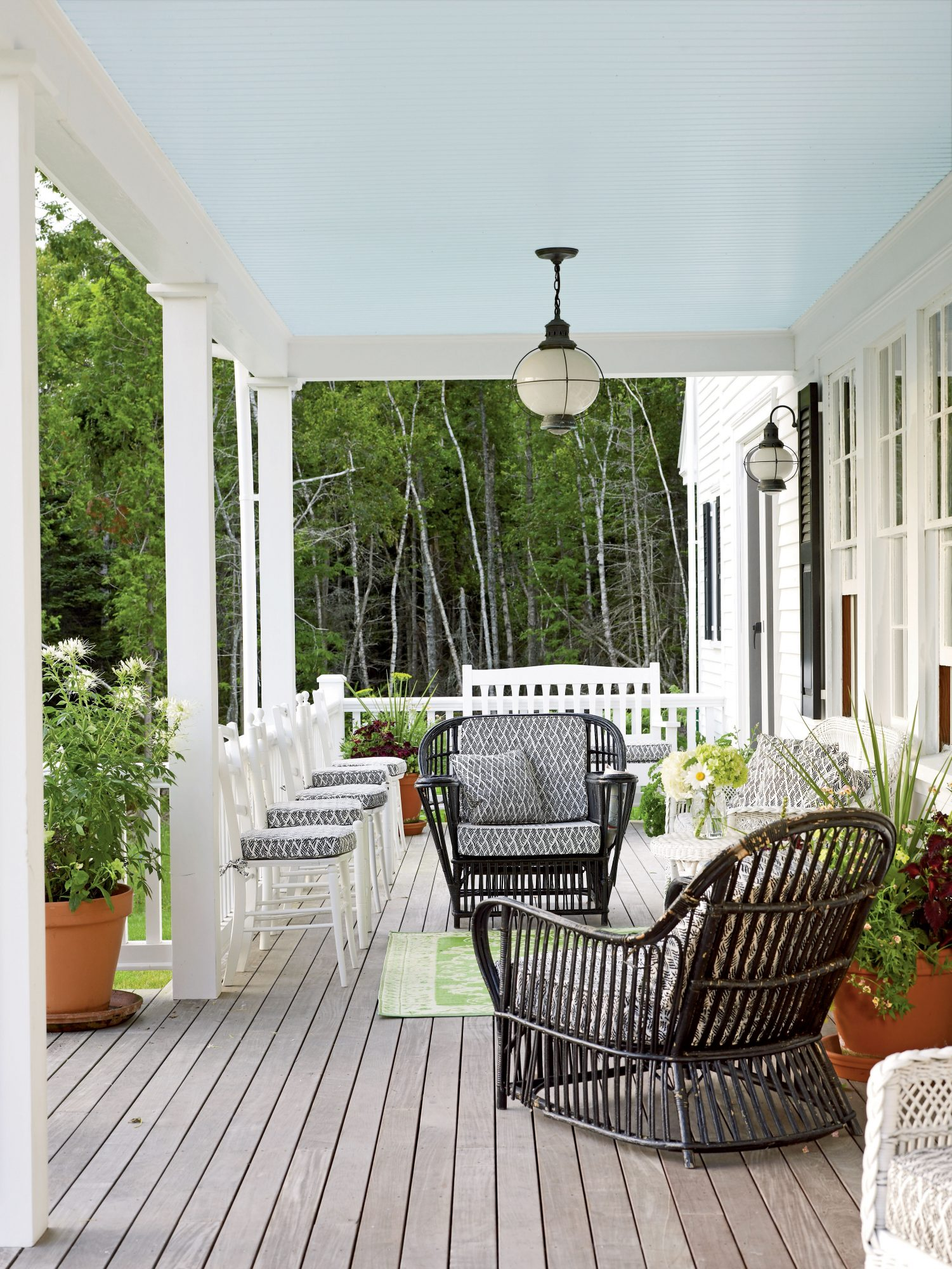 An abundant array of seating makes for a warm and inviting porch to enjoy with friends and neighbors. A lime green rug and planters add a touch of color and celebrate the surrounding foliage.