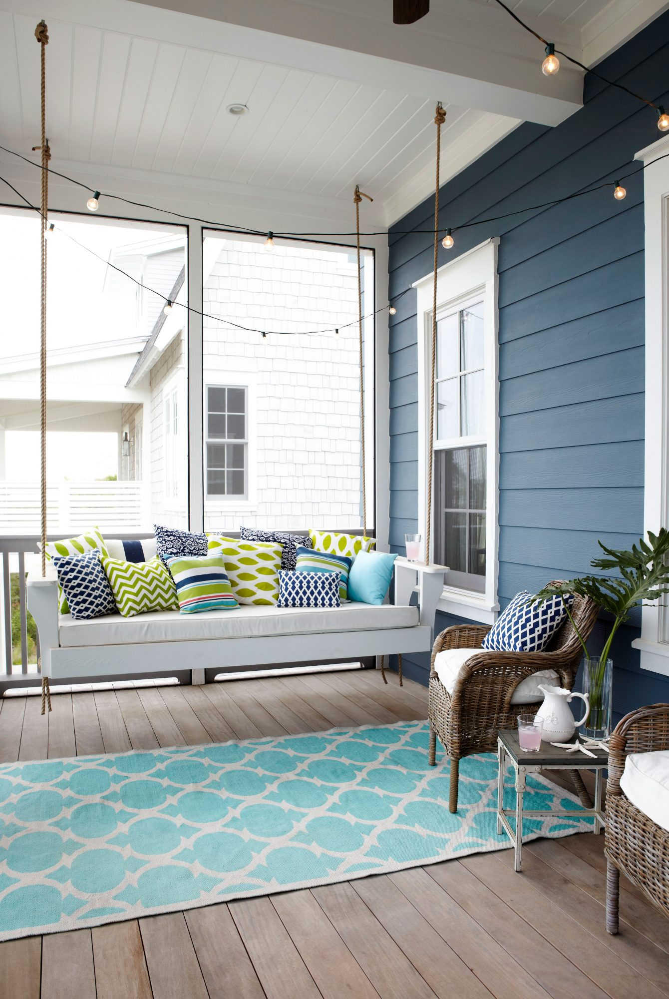 This Watersound, Florida, screened porch is the picture of relaxation, with its hanging daybed outfitted in lime green, navy, and turquoise throw pillows. A string of bistro lights add to the whimsy.