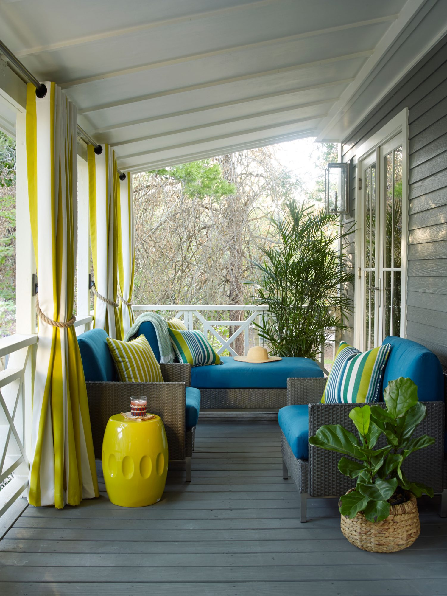 A narrow porch can make for a surprisingly accommodating outdoor room, as evidenced by our Idea Cottage in Seagrove, Florida. Designer Paige Schnell incorporated a playful palette of teal and yellow (we love the striped curtains with nautical rope ties) for a warm front porch welcome.