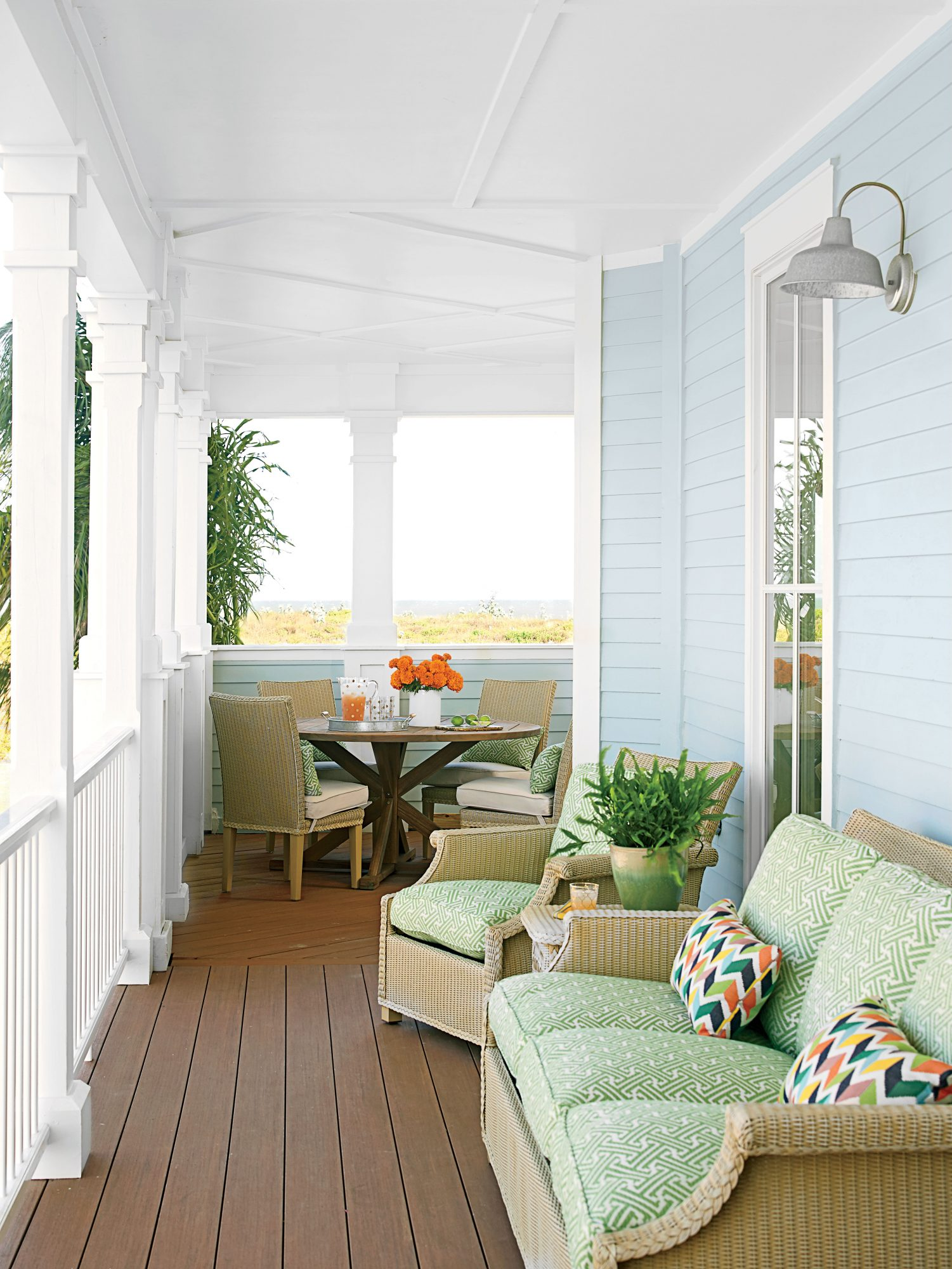The deck of our Cinnamon Shore, Texas, Showhouse has it all: a perfectly situated dining nook and a cozy conversation nook. The green Sunbrella fabric mingles softly with the pale blue exterior walls, and punchy geometric throw pillows enliven the space.