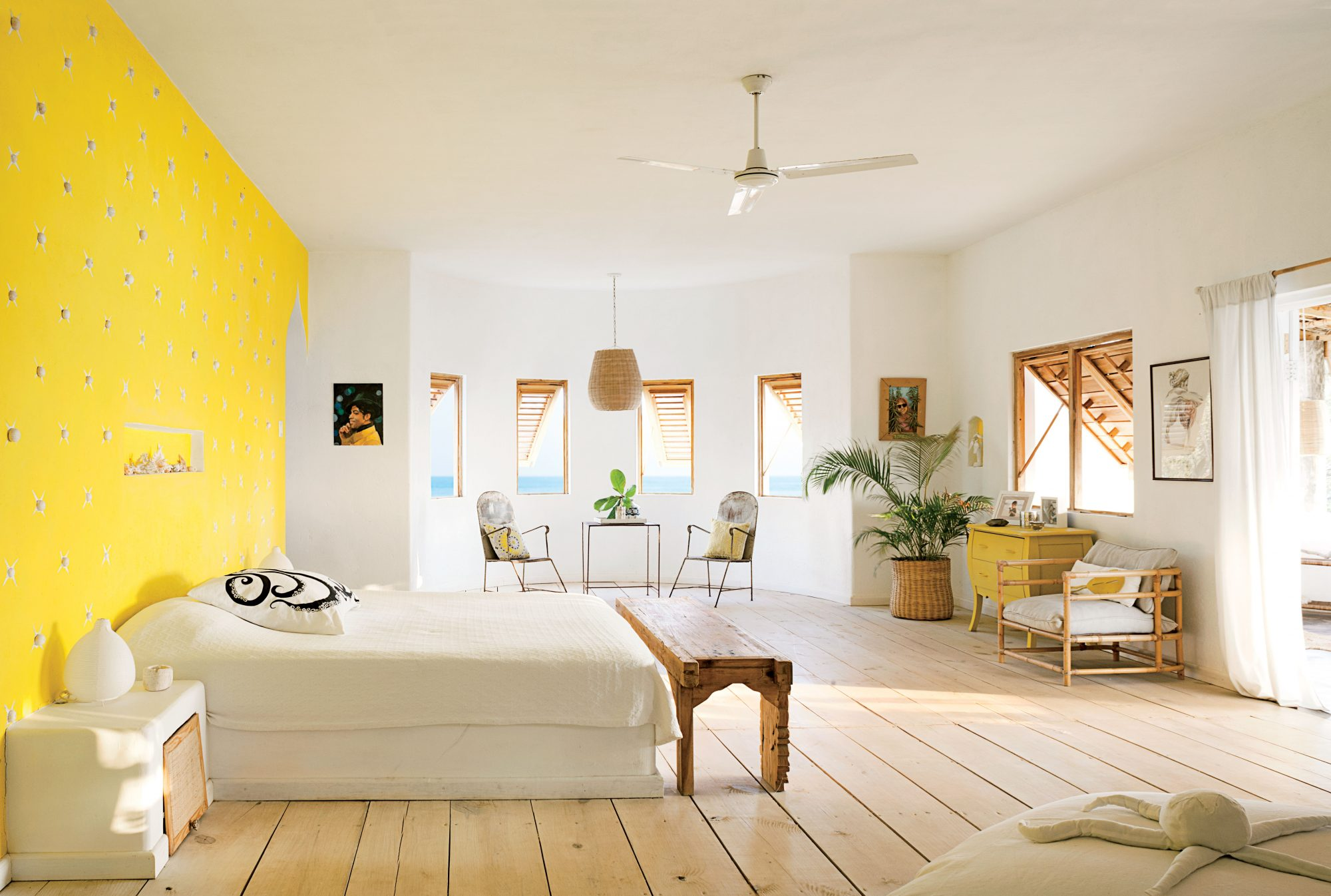 Sea urchins are affixed to the bright yellow wall of this Jamaican master bedroom, adding a fun layer of ocean-inspired texture. The rest of the room, decked in neutral tones, balances the wall's bold color.