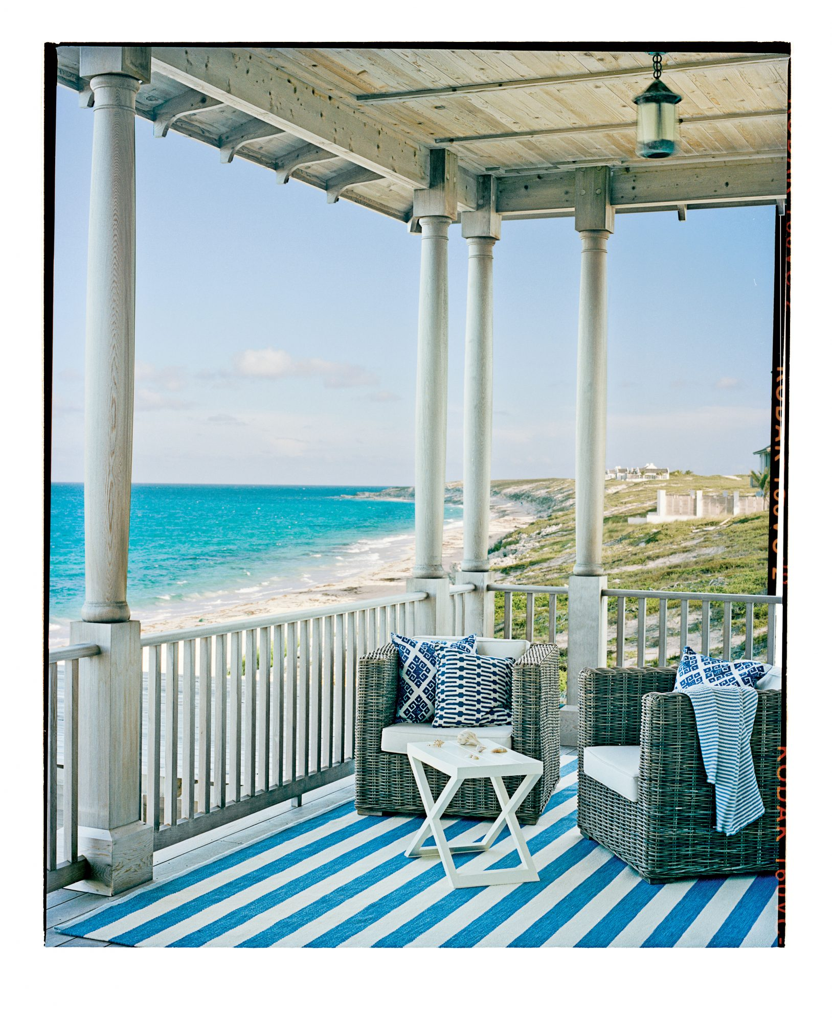 A bright blue-and-white striped rug brings a burst of color to this otherwise simple porch. Sturdy wicker chairs provide prime seating for a seaside view.