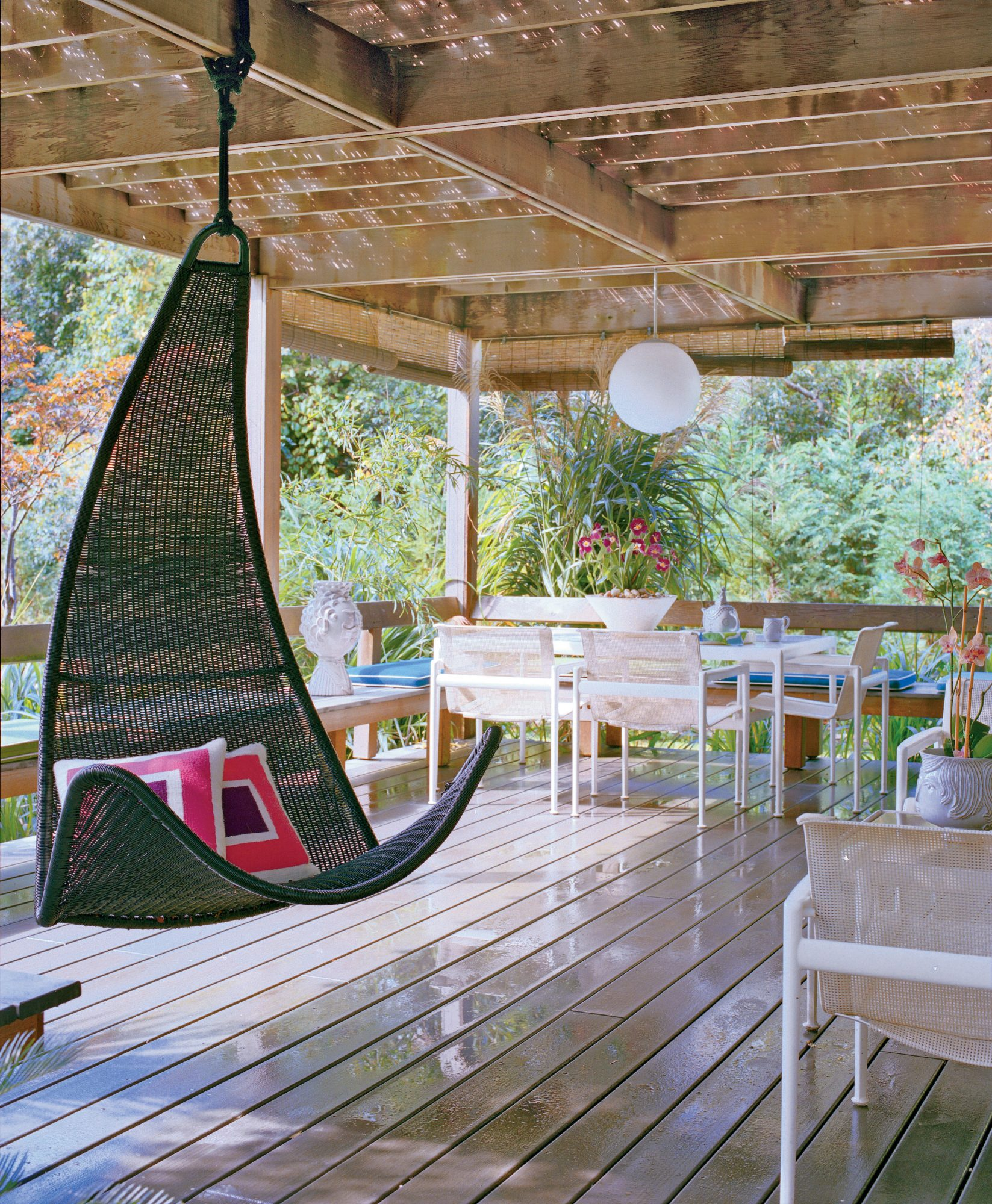 A contemporary hanging swing and a paper lantern complements the streamlined feel to this covered porch.