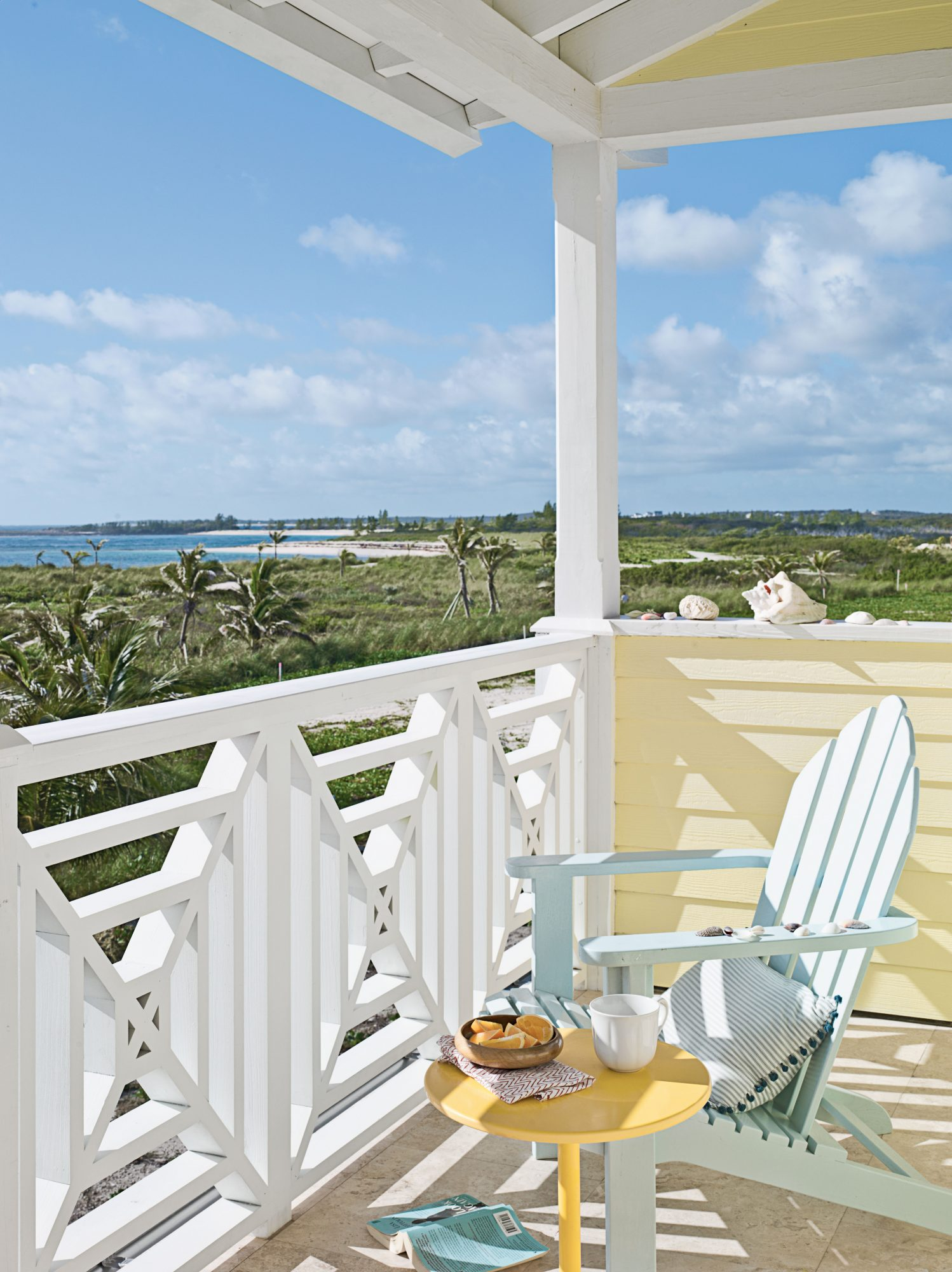 Happy yellow mixes playfully with the soft sea foam Adirondack on this Abaco Island porch.