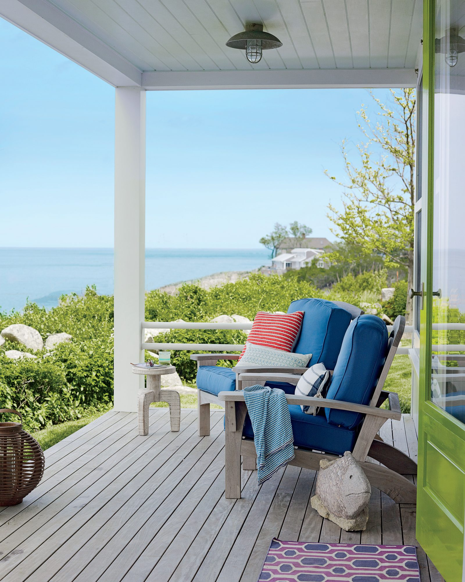 Adirondacks adorned in big blue cushions make for an inviting spot to enjoy morning coffee or happy hour cocktails on this Rockport, Massachusetts, porch.