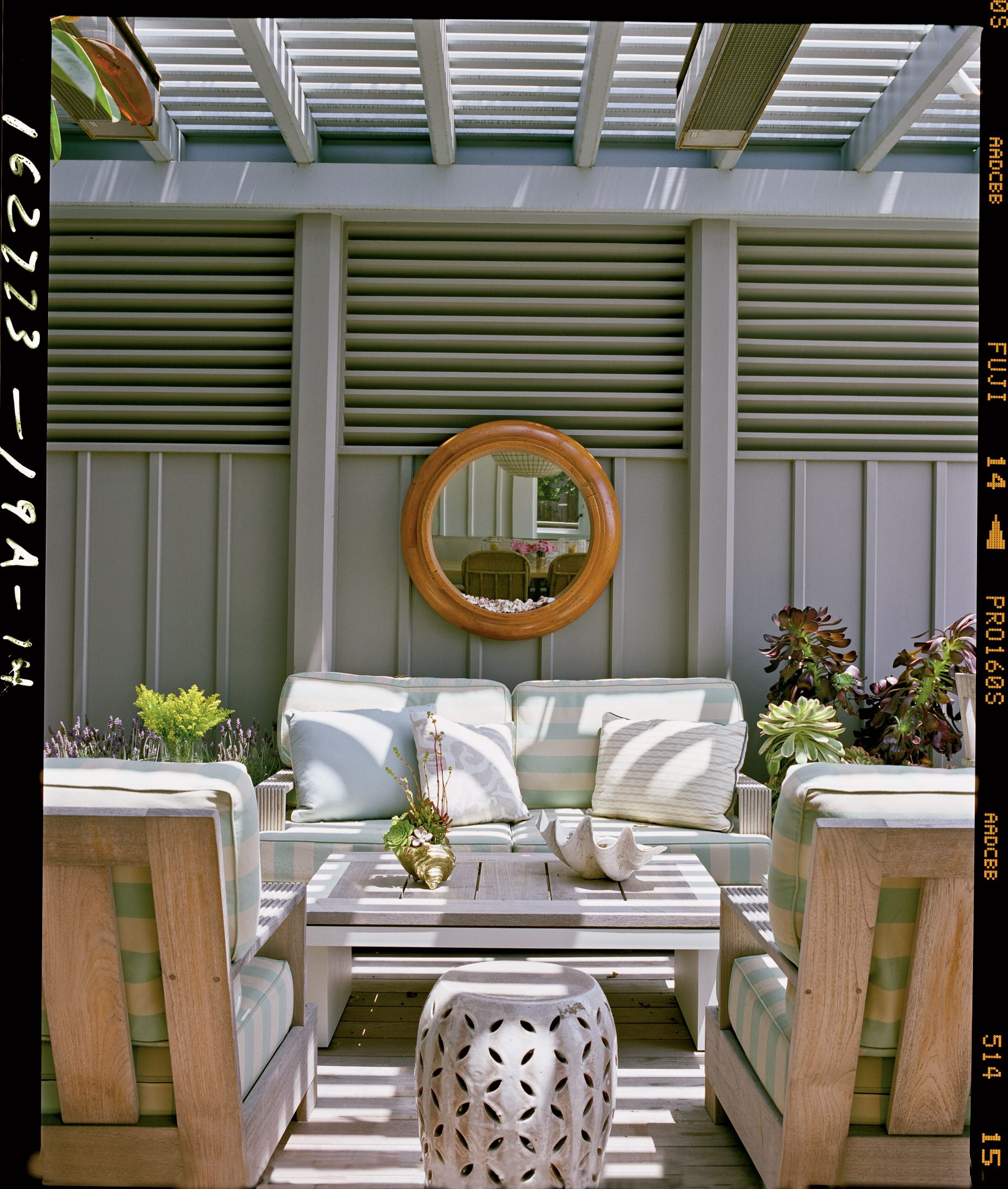 Neutral gray walls help keep this outdoor space cool, along with a light striped fabric. Railroading the stripes (running them horizontally) creates a bolder effect.