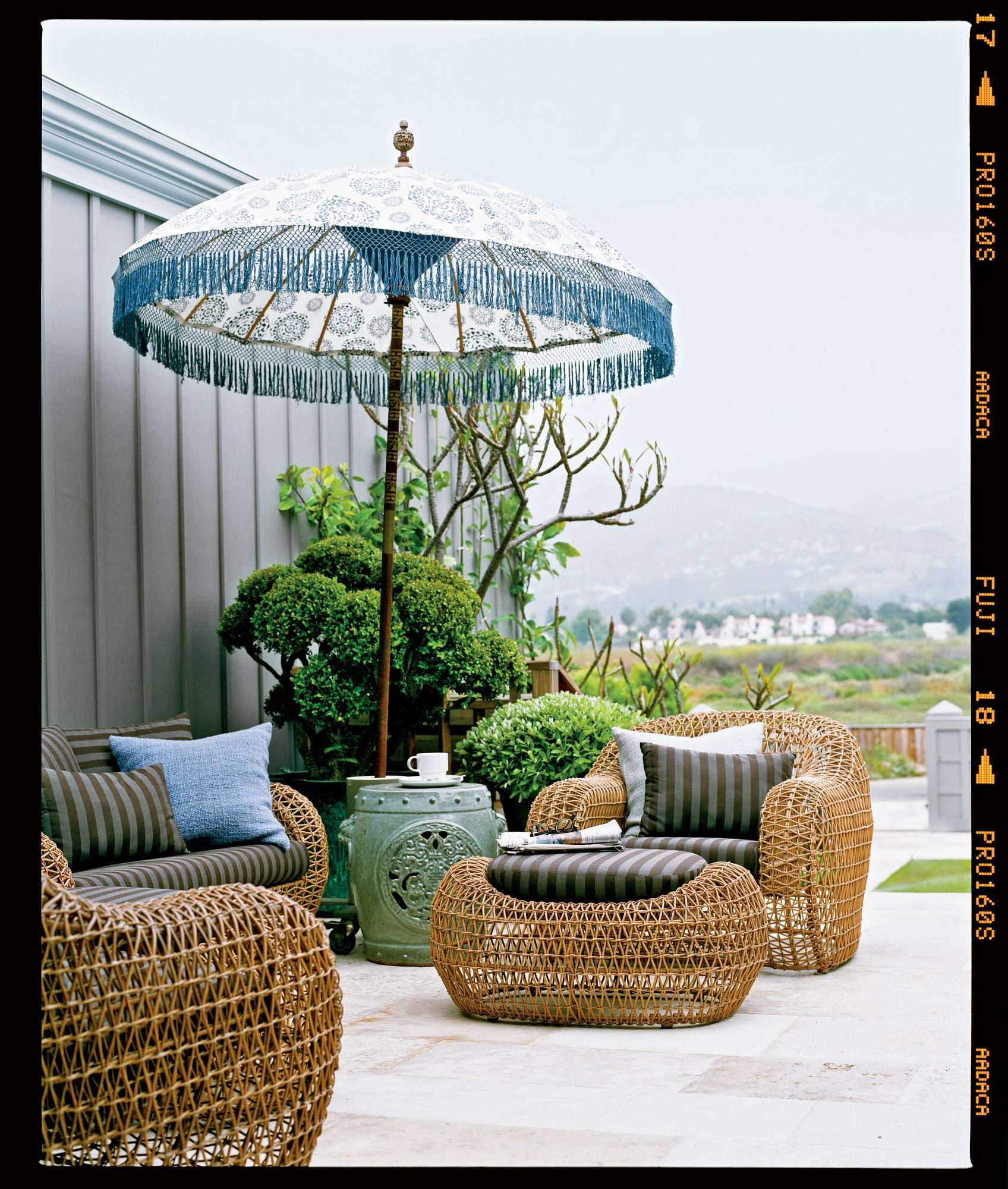 A batik-print umbrella and oversize woven furniture make a simple but stylish statement. A ceramic garden stool creates a space-saving side table on the petite patio.