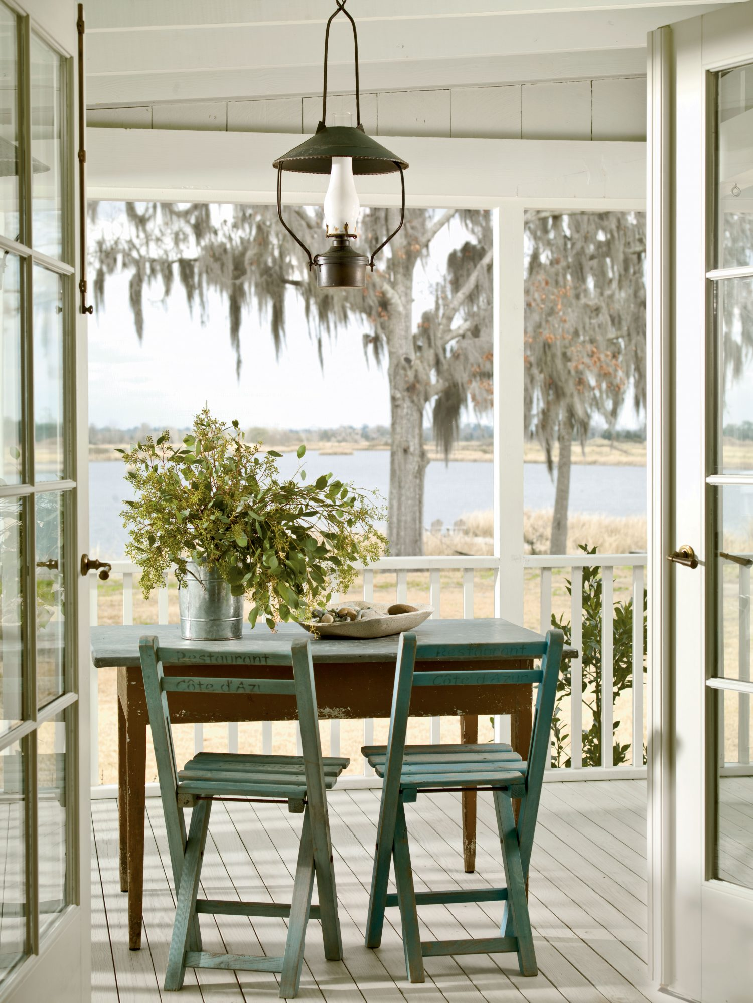 Glass French doors provide easy access to a porch, plus they bring seaside views indoors. A wooden table and chairs positioned toward the water is all this simple porch needs.
