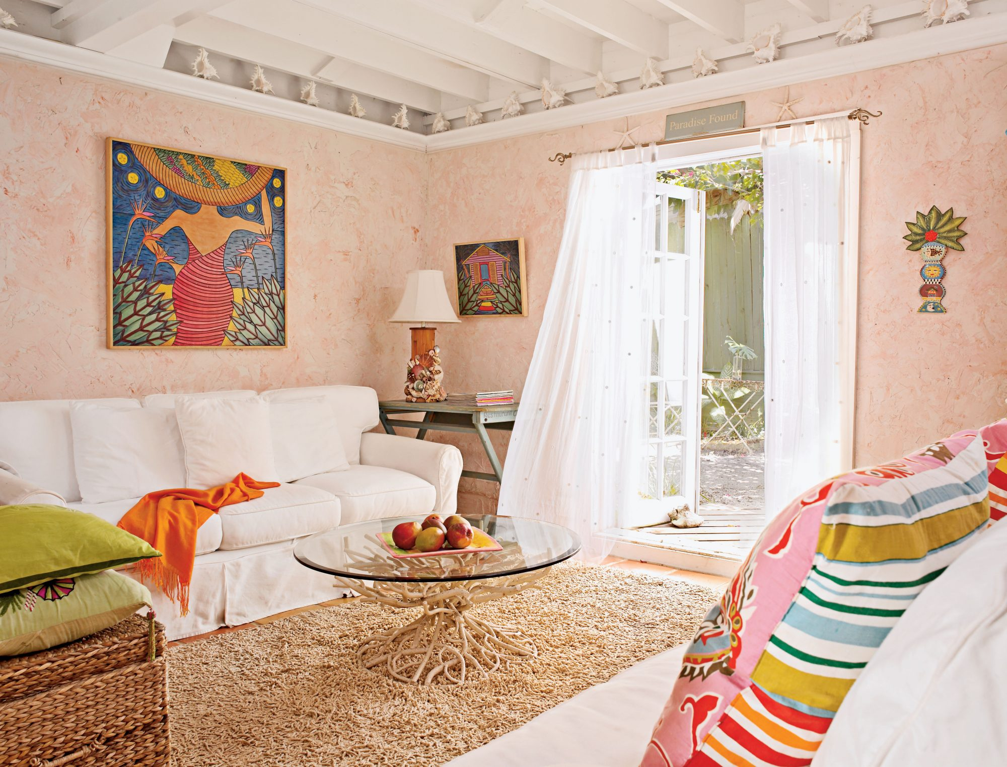 Bold artwork and pillows accent furniture slipcovered in white.