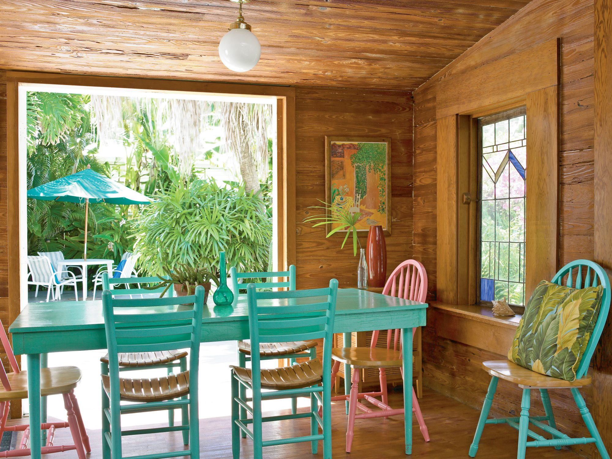 Bold print throw pillows and local artwork encourage the whimsical atmosphere, while French doors invite visitors onto the spacious deck and lush garden.