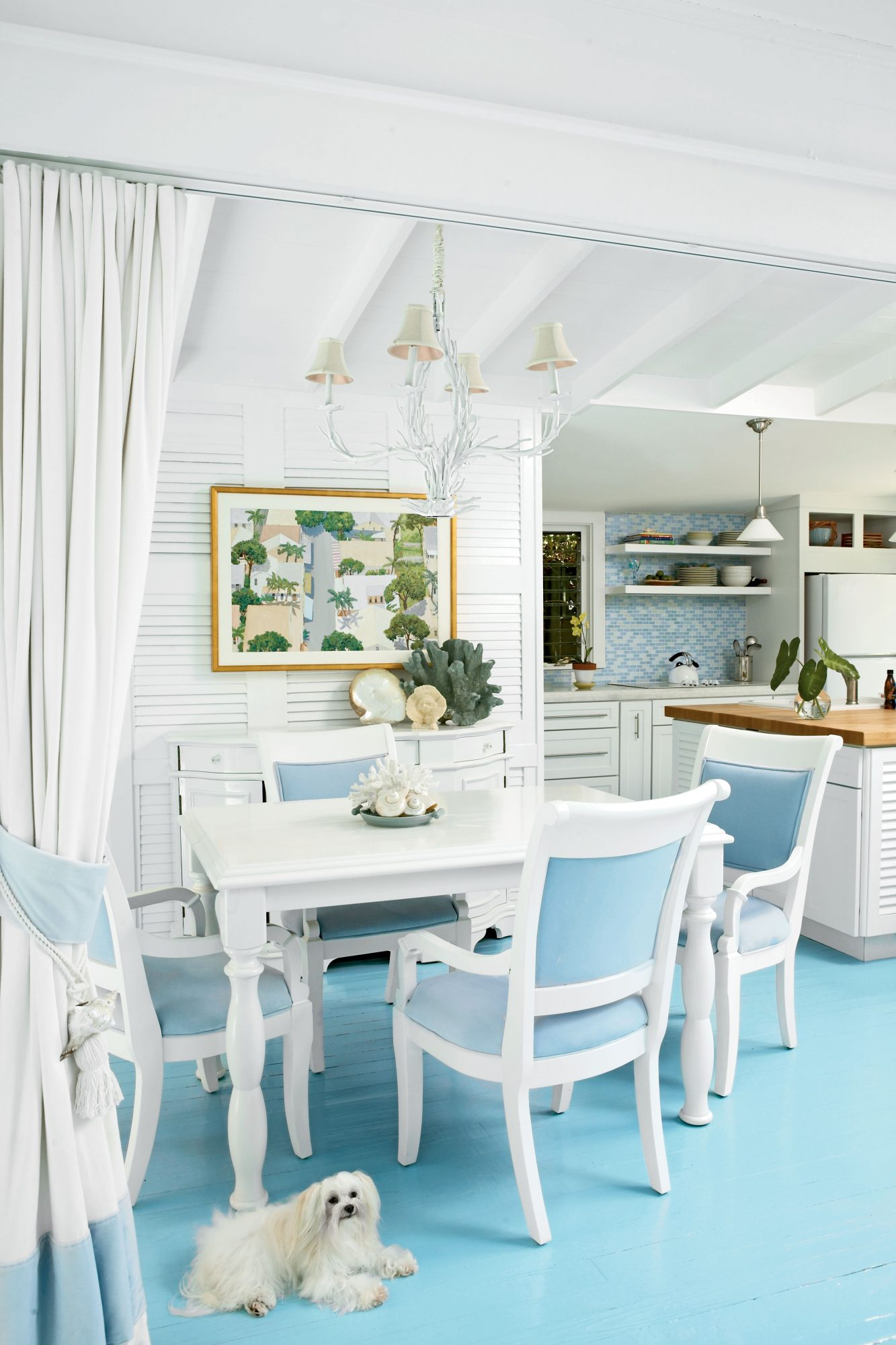 An open floorplan allows this dining room to live large, and white furniture and walls make it feel more spacious.