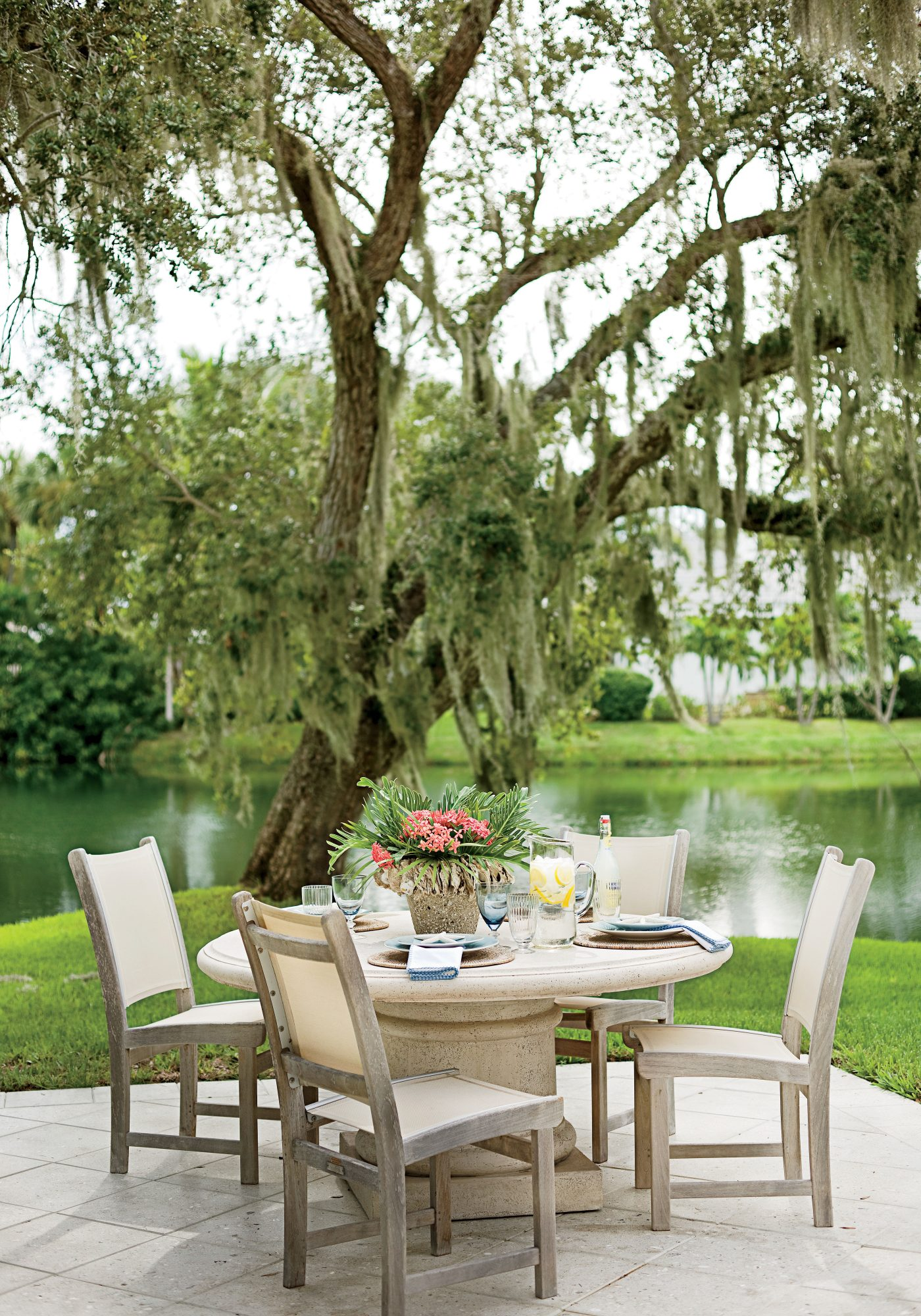 """A sturdy stone table and mesh chairs are the perfect low maintenance choice for this John's Island, Florida, patio. """"The family doesn't live here full-time, so I chose pieces they wouldn't have to store in storms and that didn't require much cleaning,"""" says designer Phoebe Howard. A quick hose down is all that's needed to ensure the space is party ready."""