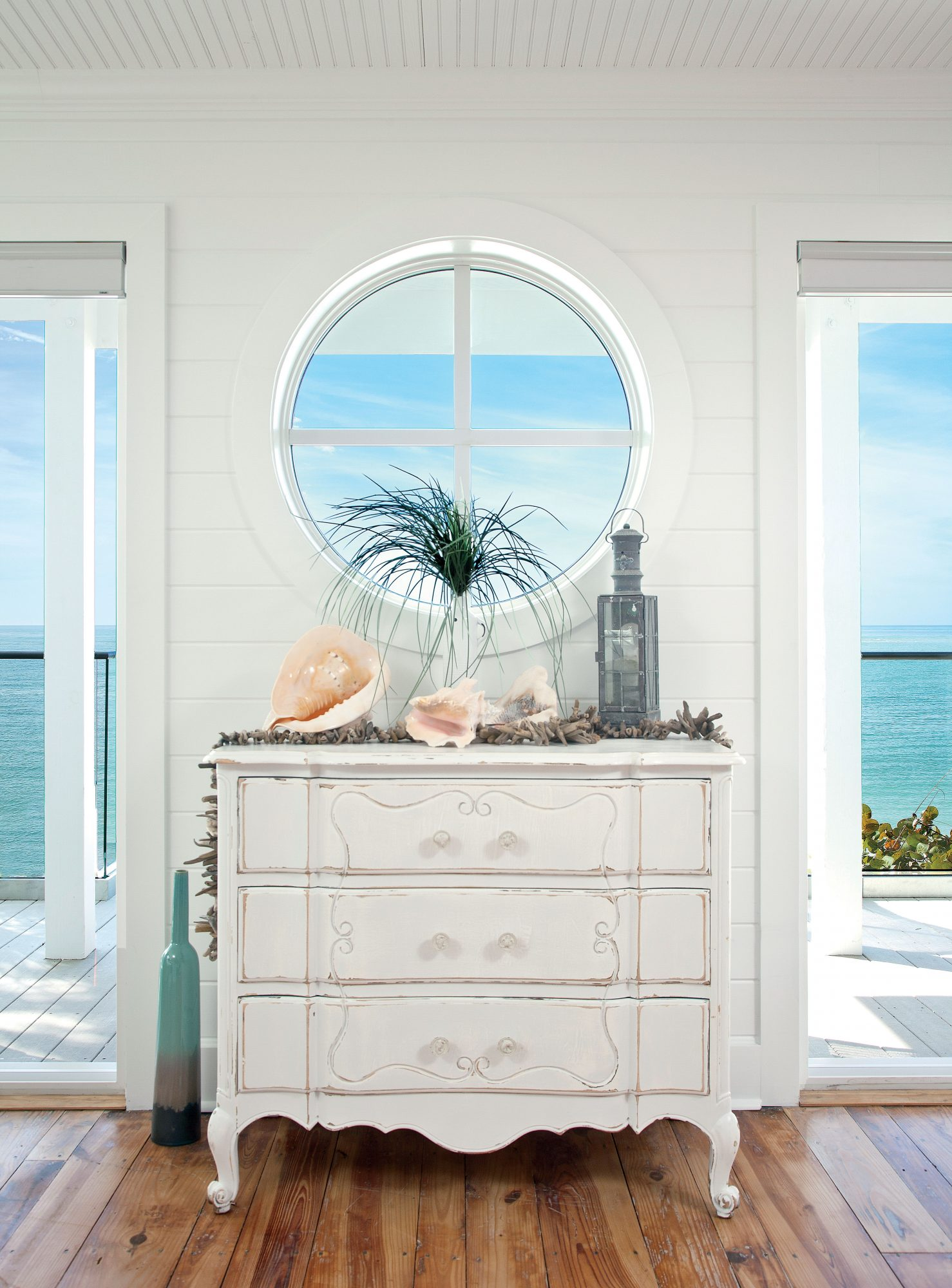 This vignette—in a bright beach house on Anna Maria Island, Florida—cleverly features a circular window in place of a more traditional mirror or piece of art. The buffet's playful curves and distressed finish provide a nice contrast to the clean, geometri