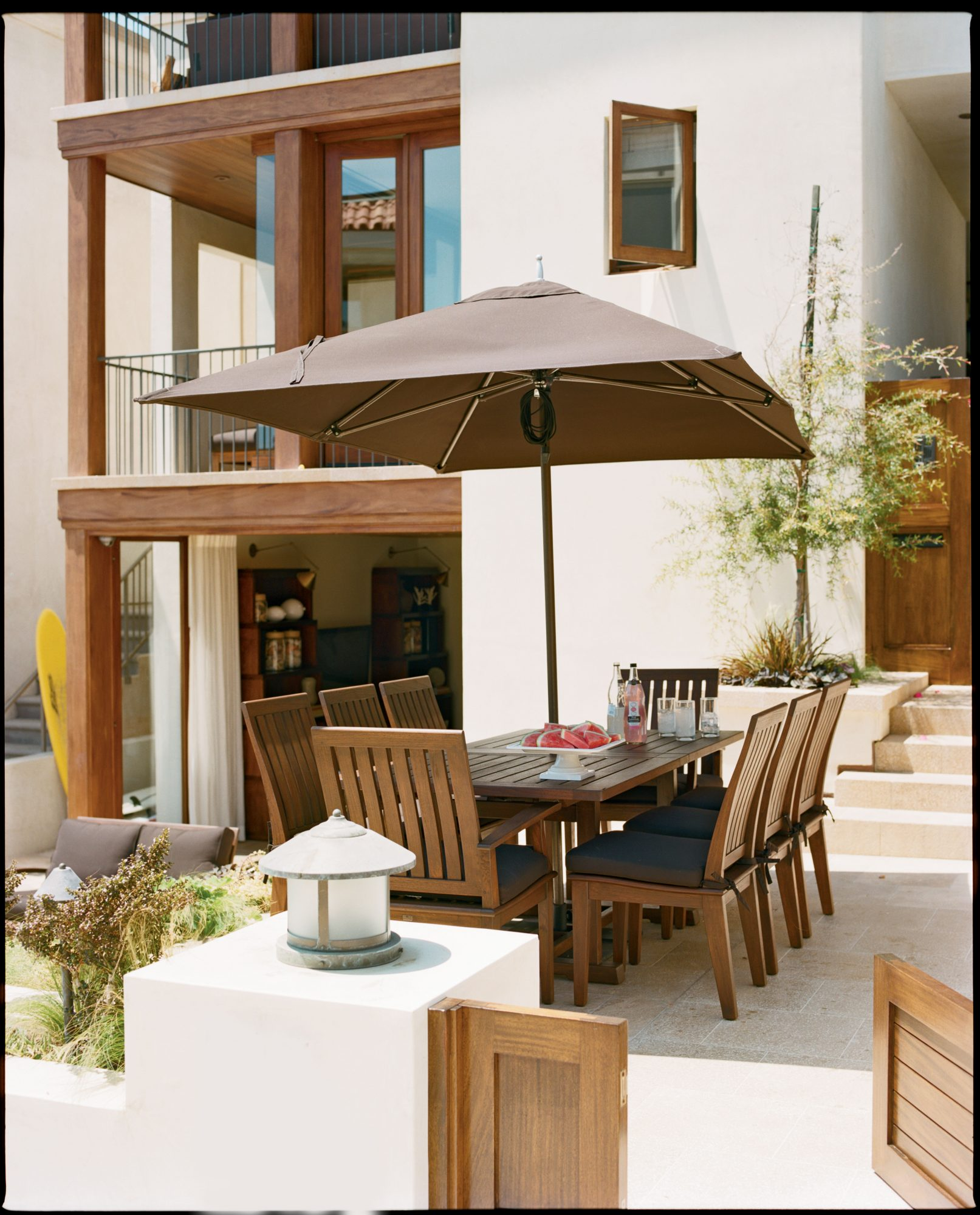 With a straight-edge table and stylishly modern umbrella, this outdoor patio keeps entertaining simple. A multilevel patio breaks the space up into separate outdoor rooms.