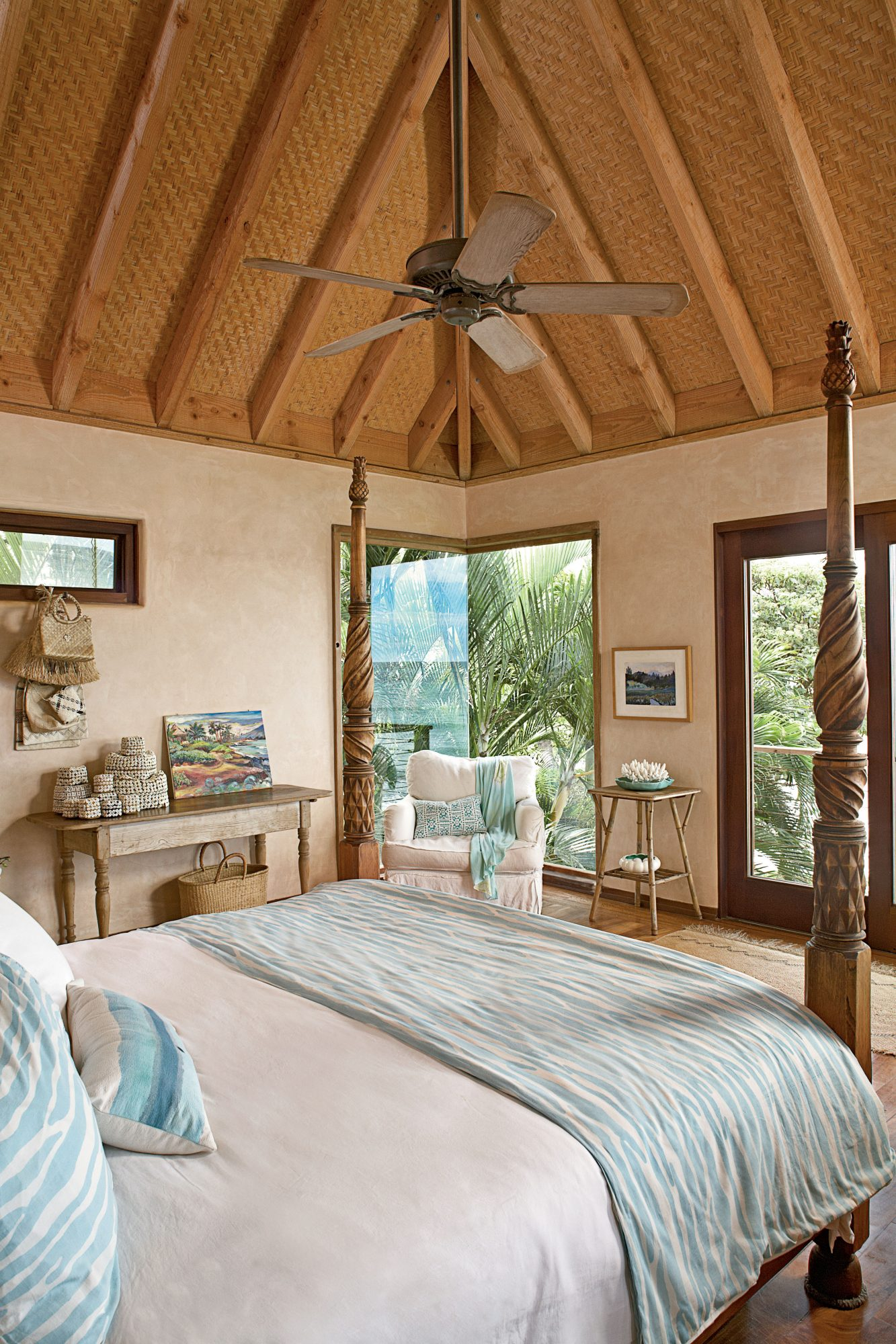 This Maui bedroom is full of island style. The ceiling's exposed rafters and bamboo ceiling, carved bedposts, and nearly floor-to-ceiling windows give the space a Swiss Family Robinson-like feel.
