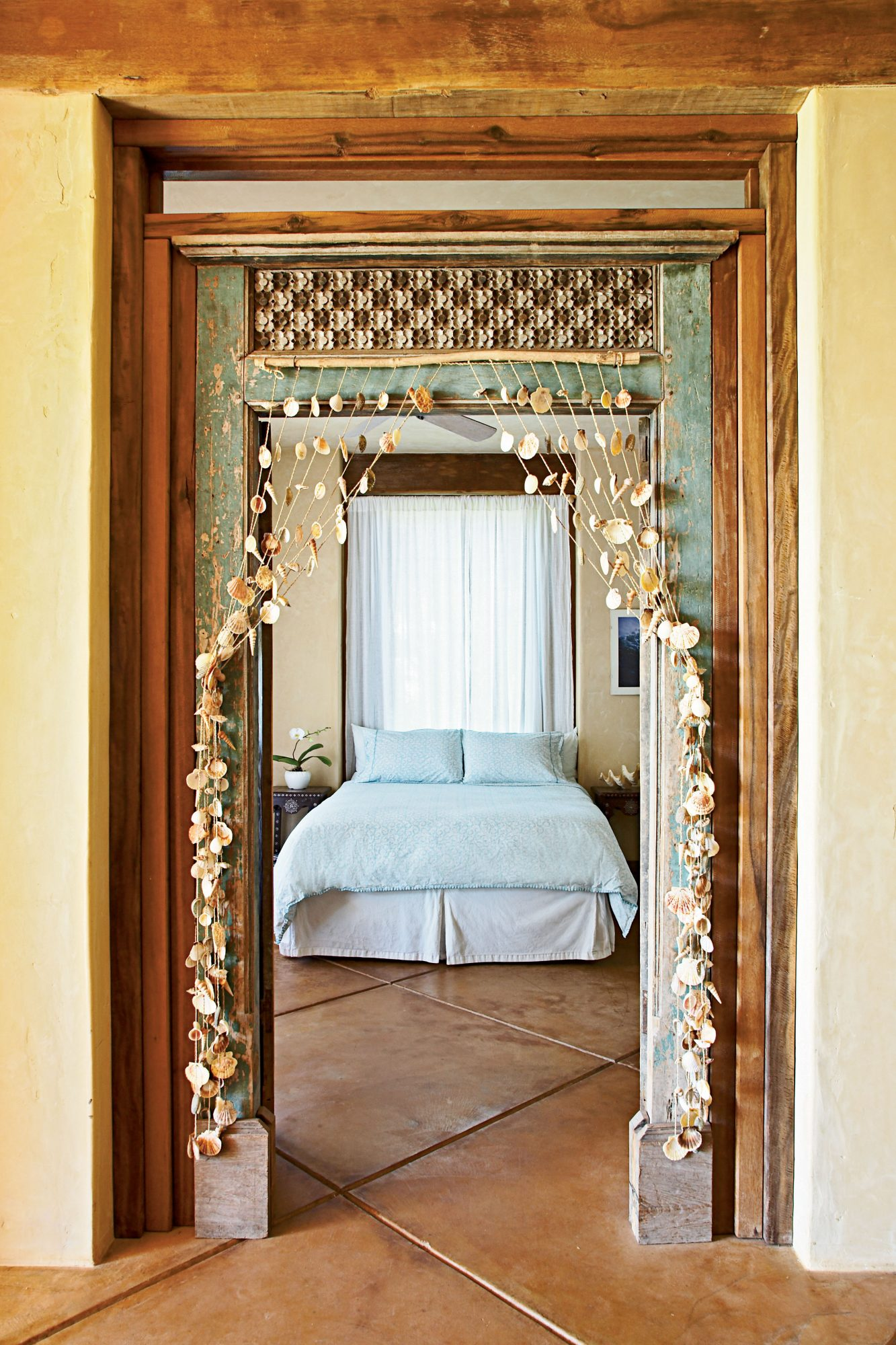 The seashell curtain hanging over the entry to this bedroom is a fun reminder that the Pacific Ocean is just outside.