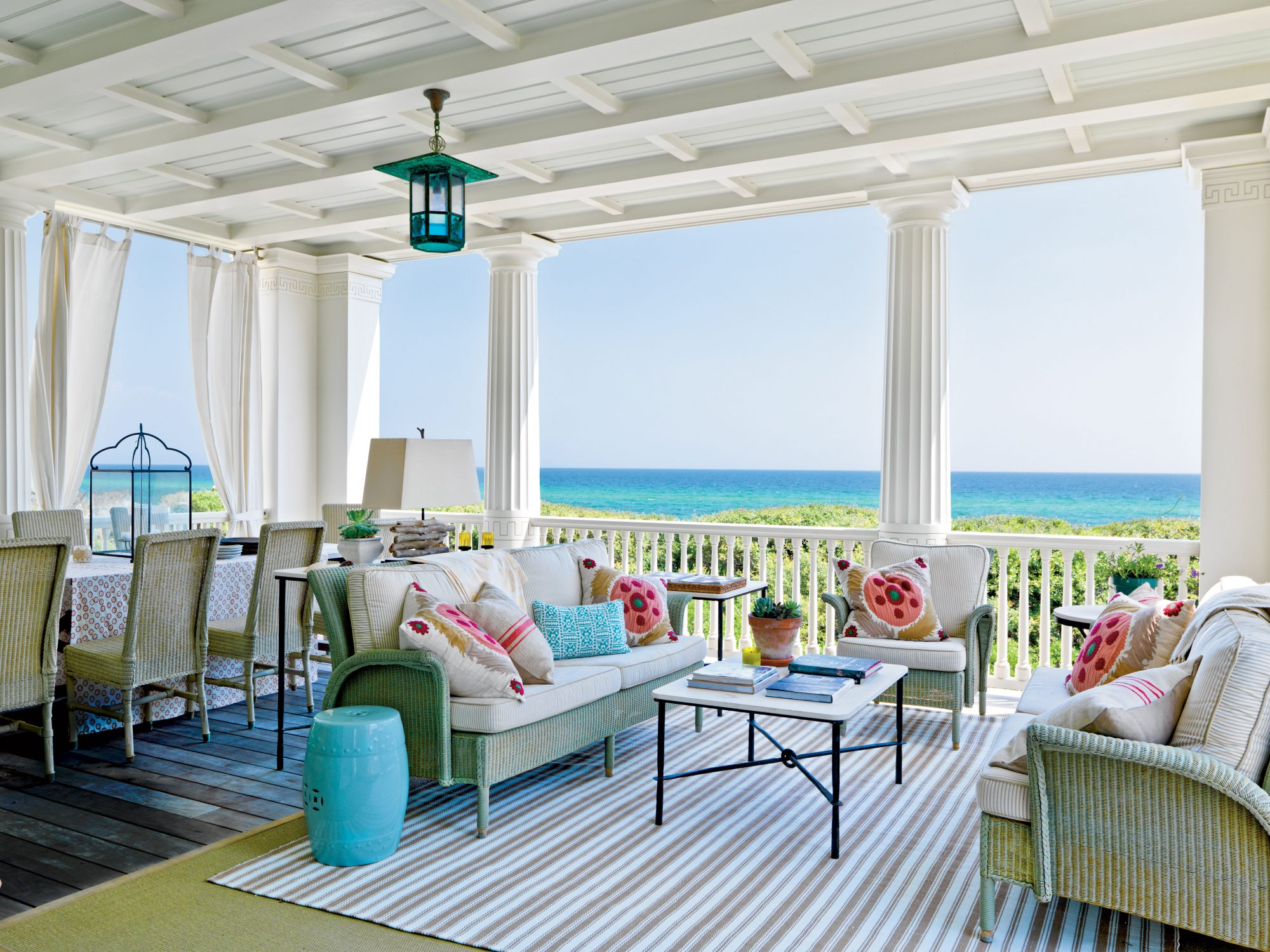 Brightly hued suzani throw pillows add a pop of color to this Gulf Coast perch. A striped indoor/outdoor rug provides ample cushioning for bare feet.