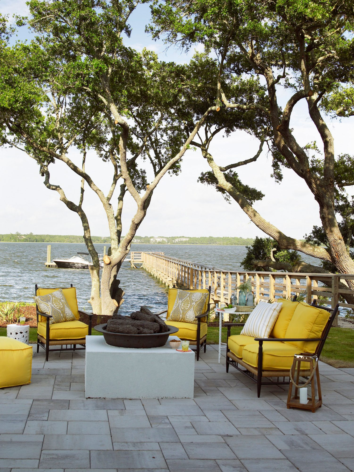 The patio of the Daniel Island Showhouse is the perfect outdoor hangout space along the Wando river, with plenty of cushy seating and a fun fire pit.