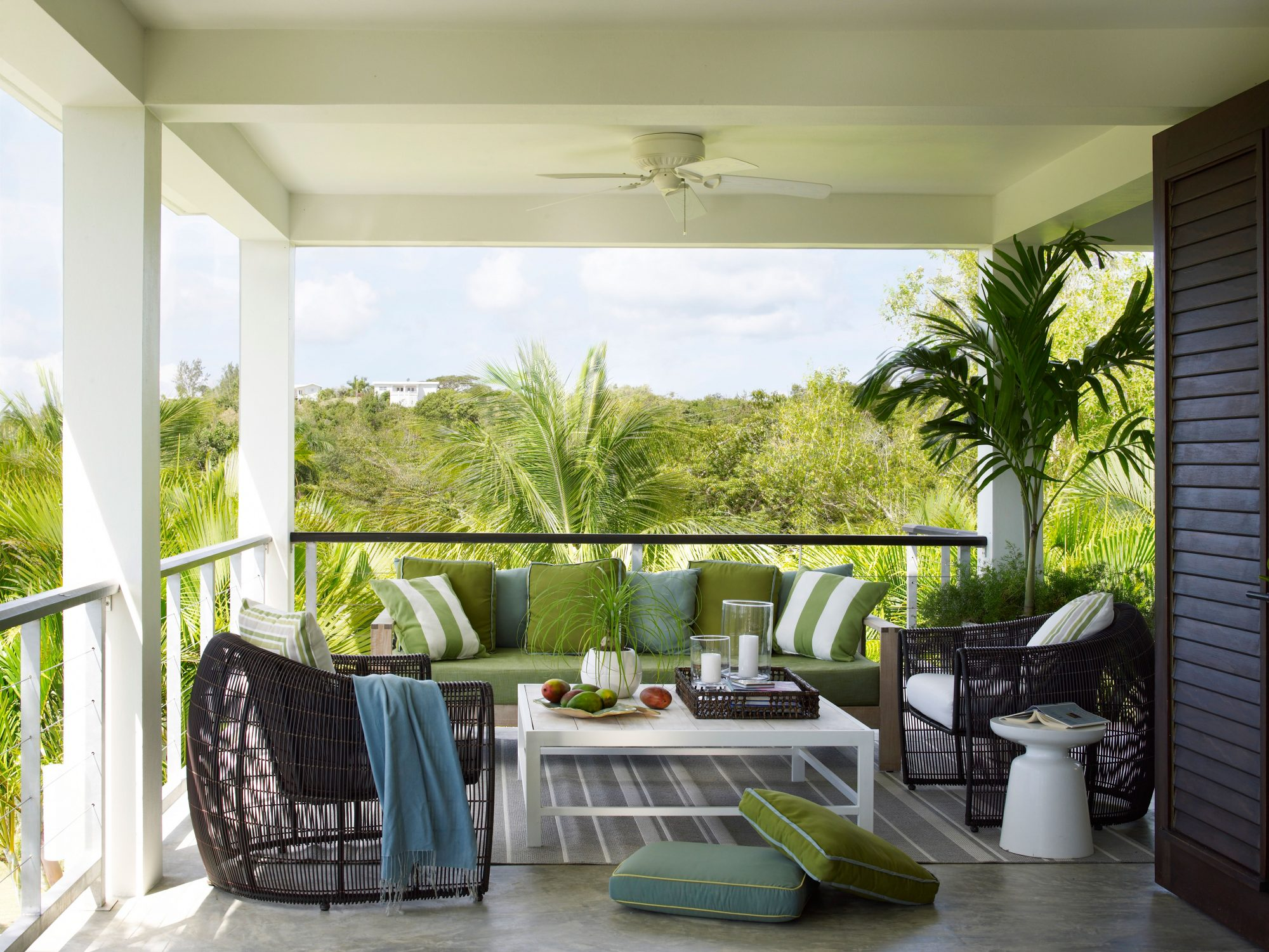 This porch on the island of Vieques in Puerto Rico is airy and inviting, thanks to the well cushioned teak sofa and lounge chairs. The palette perfectly echoes the beautiful views beyond.