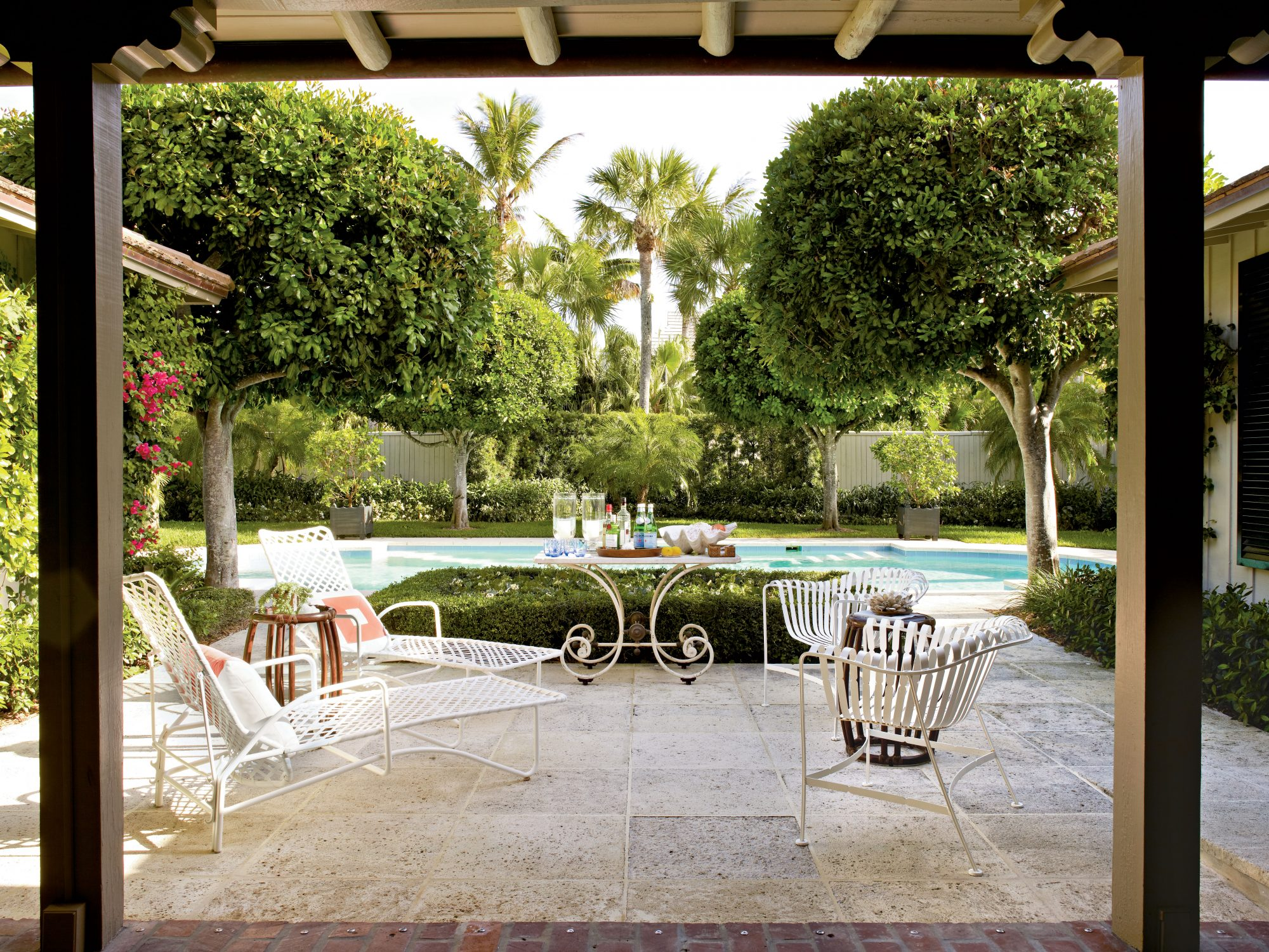 A shady loggia connects to the main house for easy entertaining. Vintage white furniture beckons swimmers to lounge in the sun for a while.