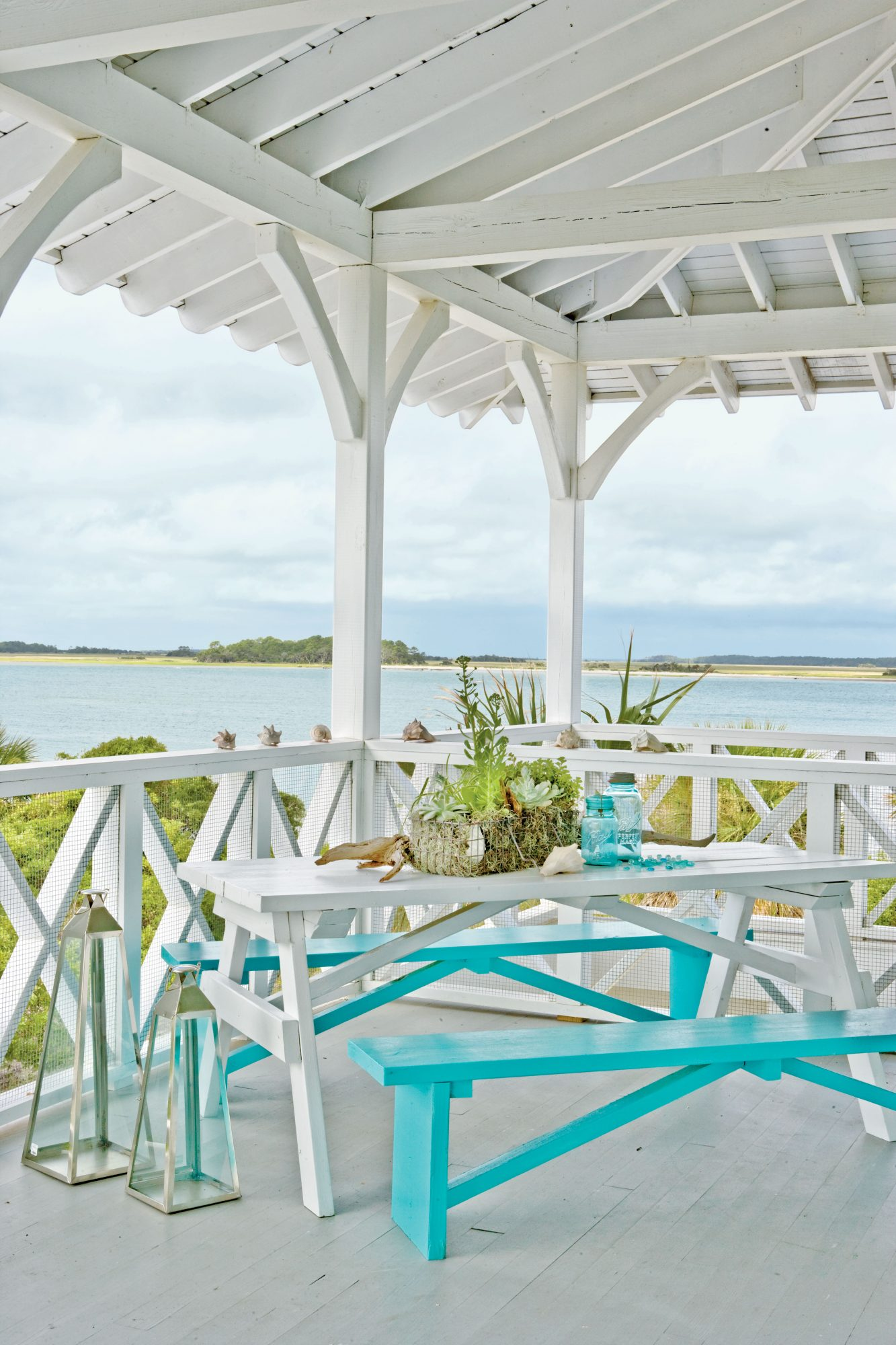 Endless vistas of chartreuse marsh grass and blue-gray water are the focal point of this breezy porch. A white and turquoise picnic set adds a cheerful vibe.