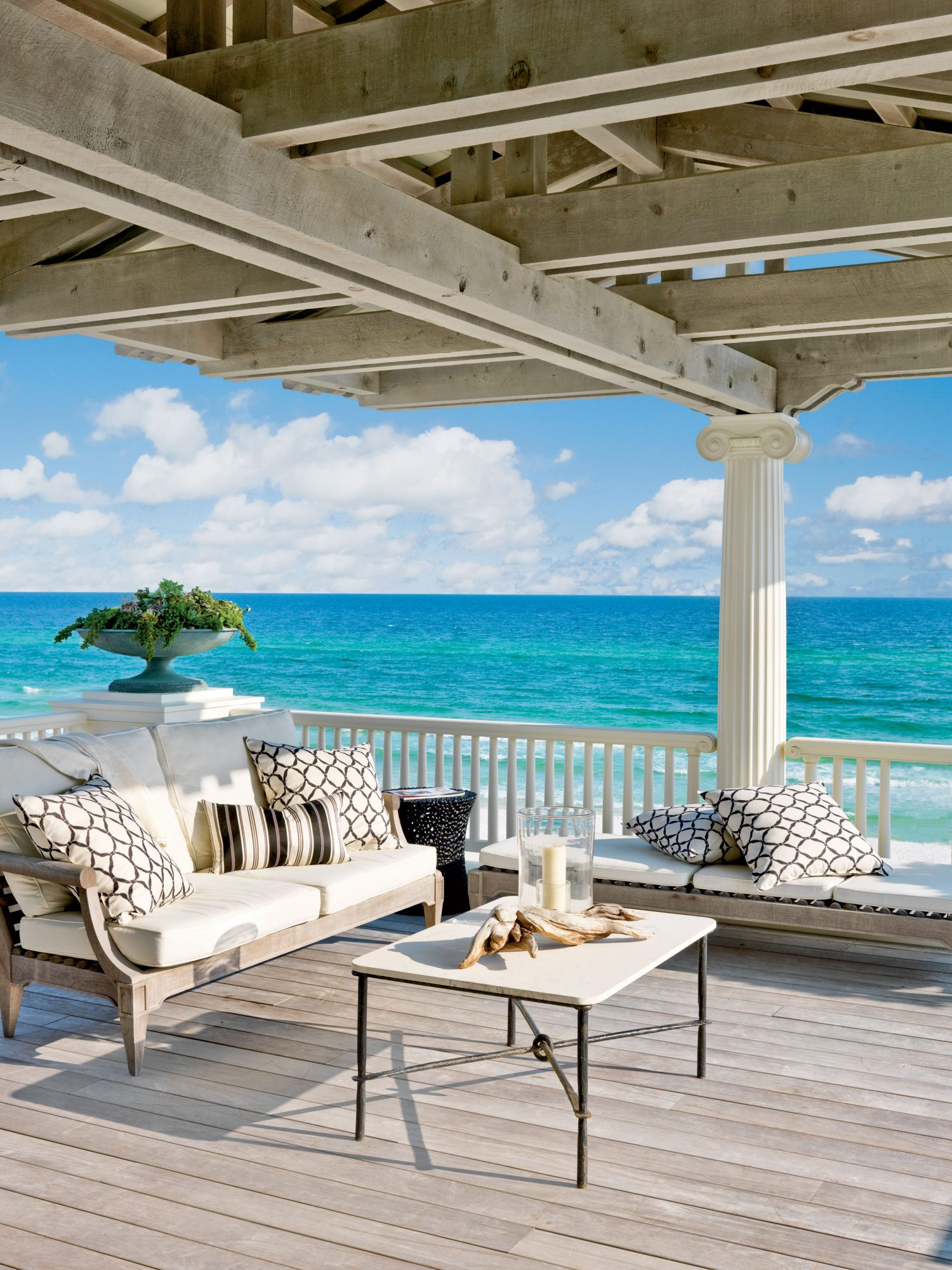 Contrasting building materials, like knotty wood beams and unfinished flooring are offset by Ionic fluted columns and classic railings for plenty of architectural interest on this porch. The décor leans toward neutral, letting the eye be drawn to the turquoise and blue water beyond.