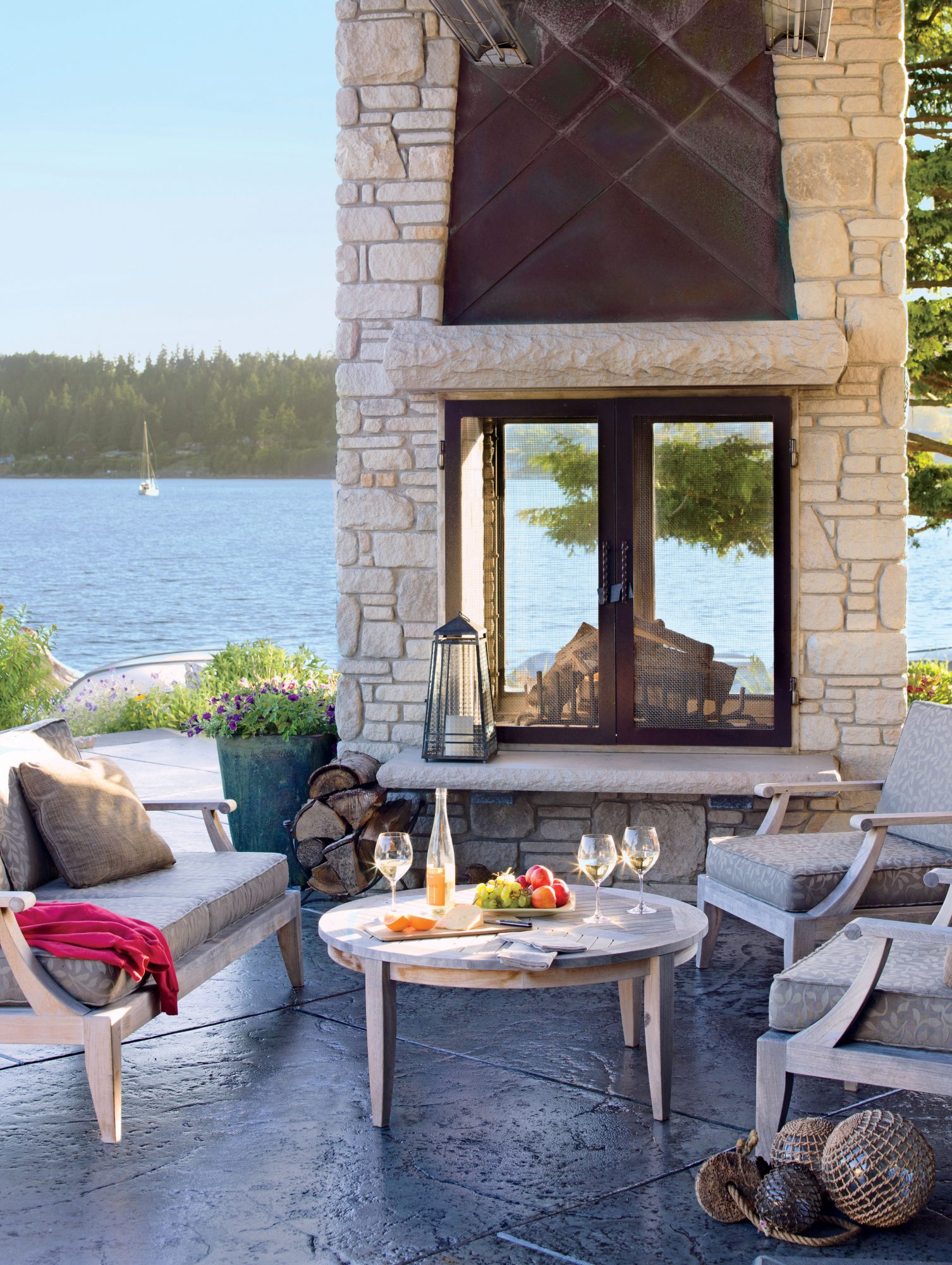 Get the Look: The furniture is from Westminster Teak. The flooring is concrete.                                       A glass-framed fireplace anchors this warm and cozy patio on Fidalgo Island, Washington.