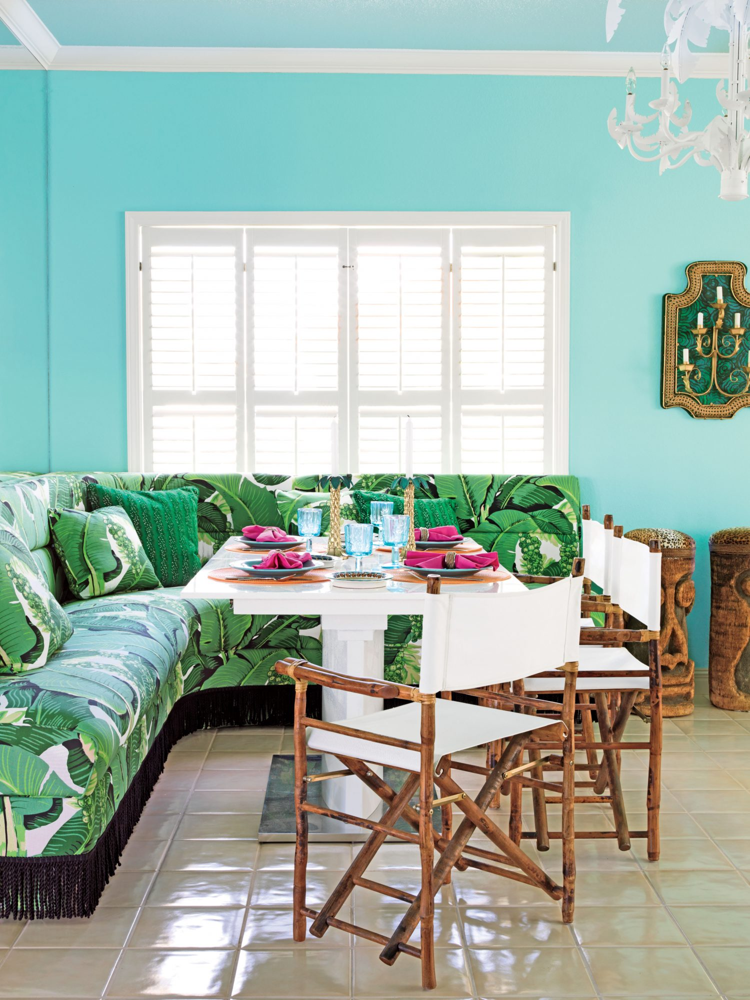 The bold, leafy pattern on this South Padre Island, Texas, banquette creates a tropical atmosphere. Bright eggshell paint, vintage tiki stools, and folding director's-style chairs further enhance the effect.
